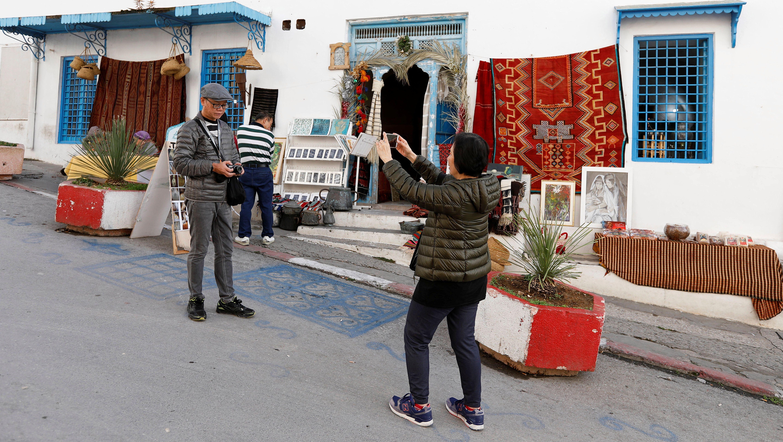 A tourist poses for a picture in Sidi Bou Said, an attractive tourist destination near Tunis, Tunisia January 7, 2019.