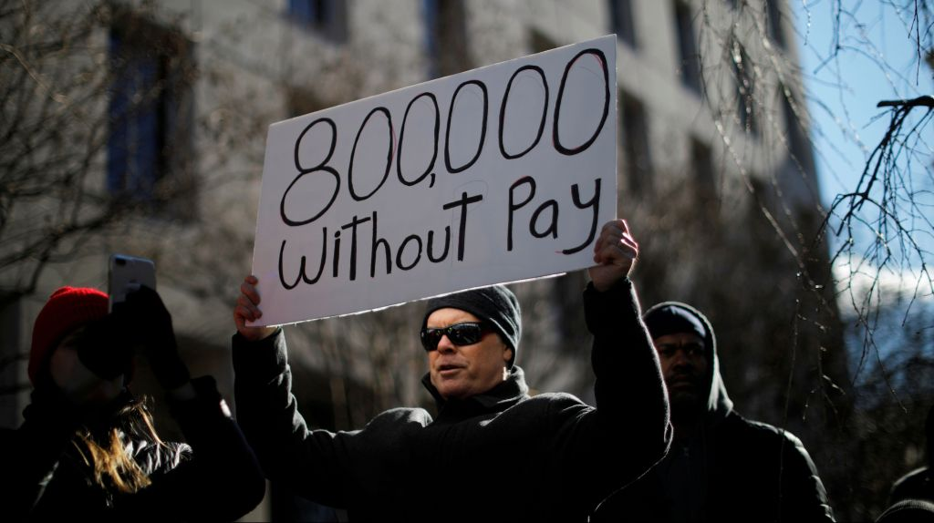 "A demonstrator holds a sign, signifying hundreds of thousands of federal employees who won't be receiving their paychecks as a result of the partial government shutdown, during a ""Rally to End the Shutdown"" in Washington,"