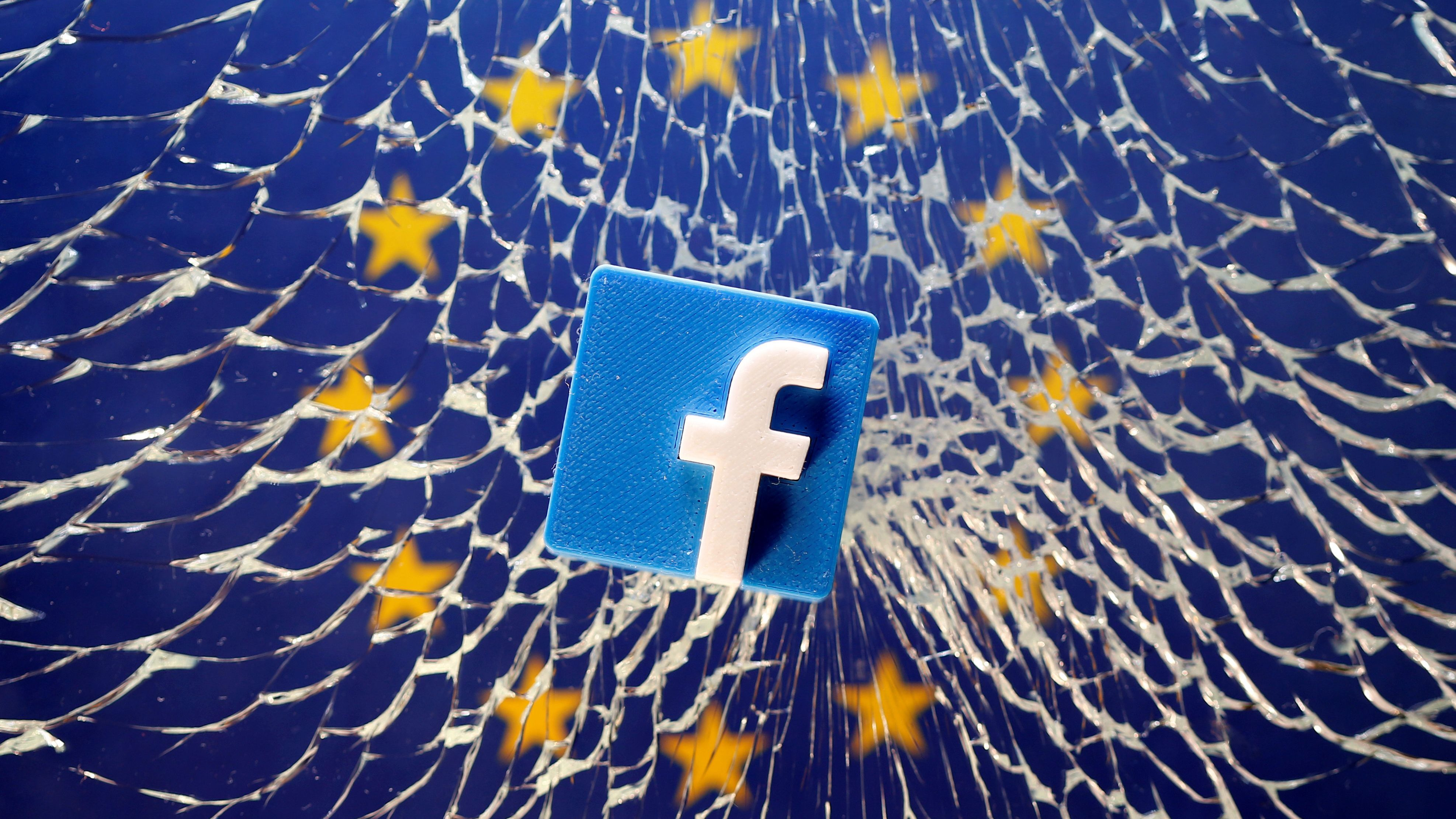 A 3D printed Facebook logo is placed on broken glass above a printed EU flag in this illustration