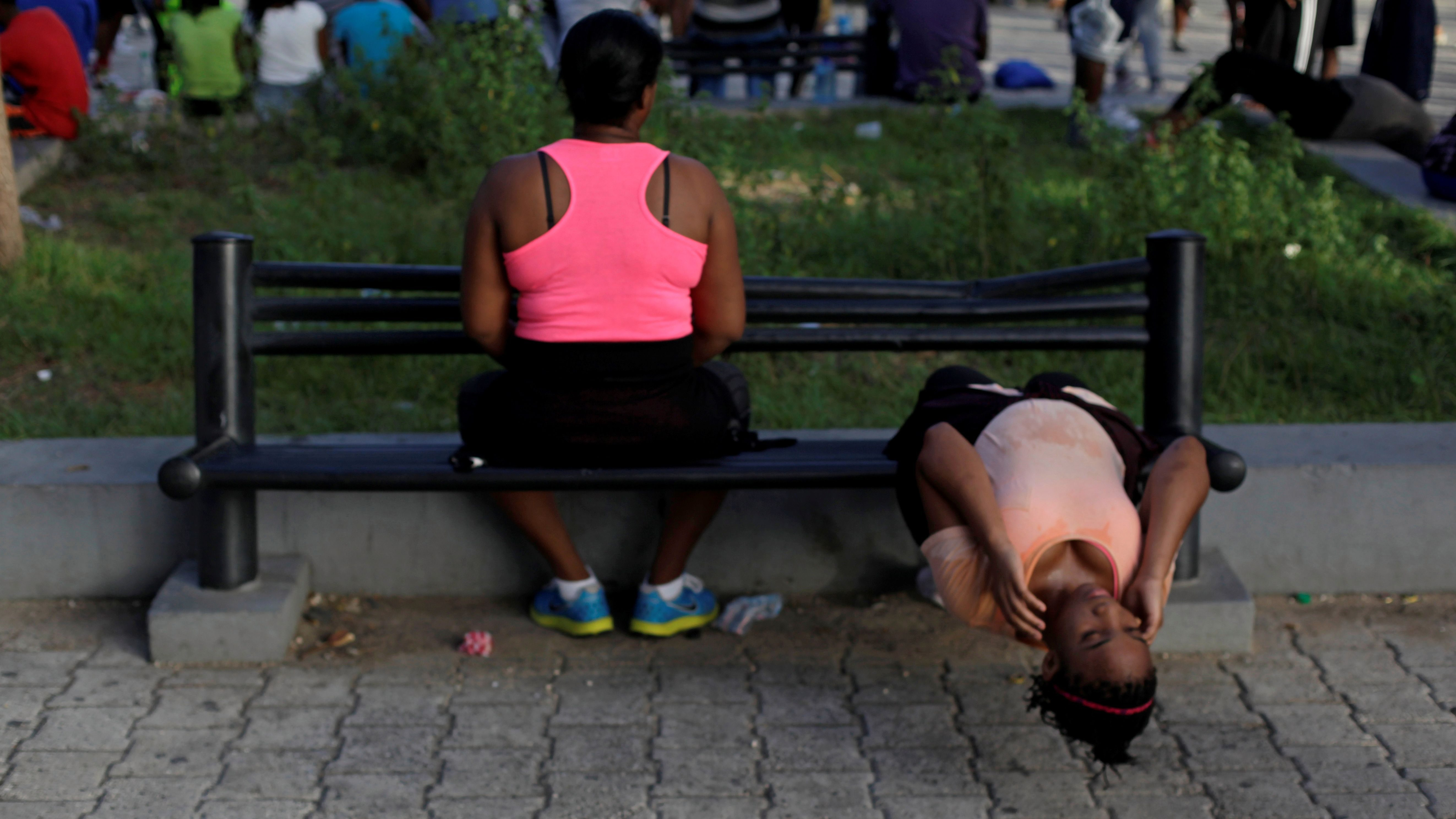 A woman does crunches on a bench at a public park in Port-au-Prince