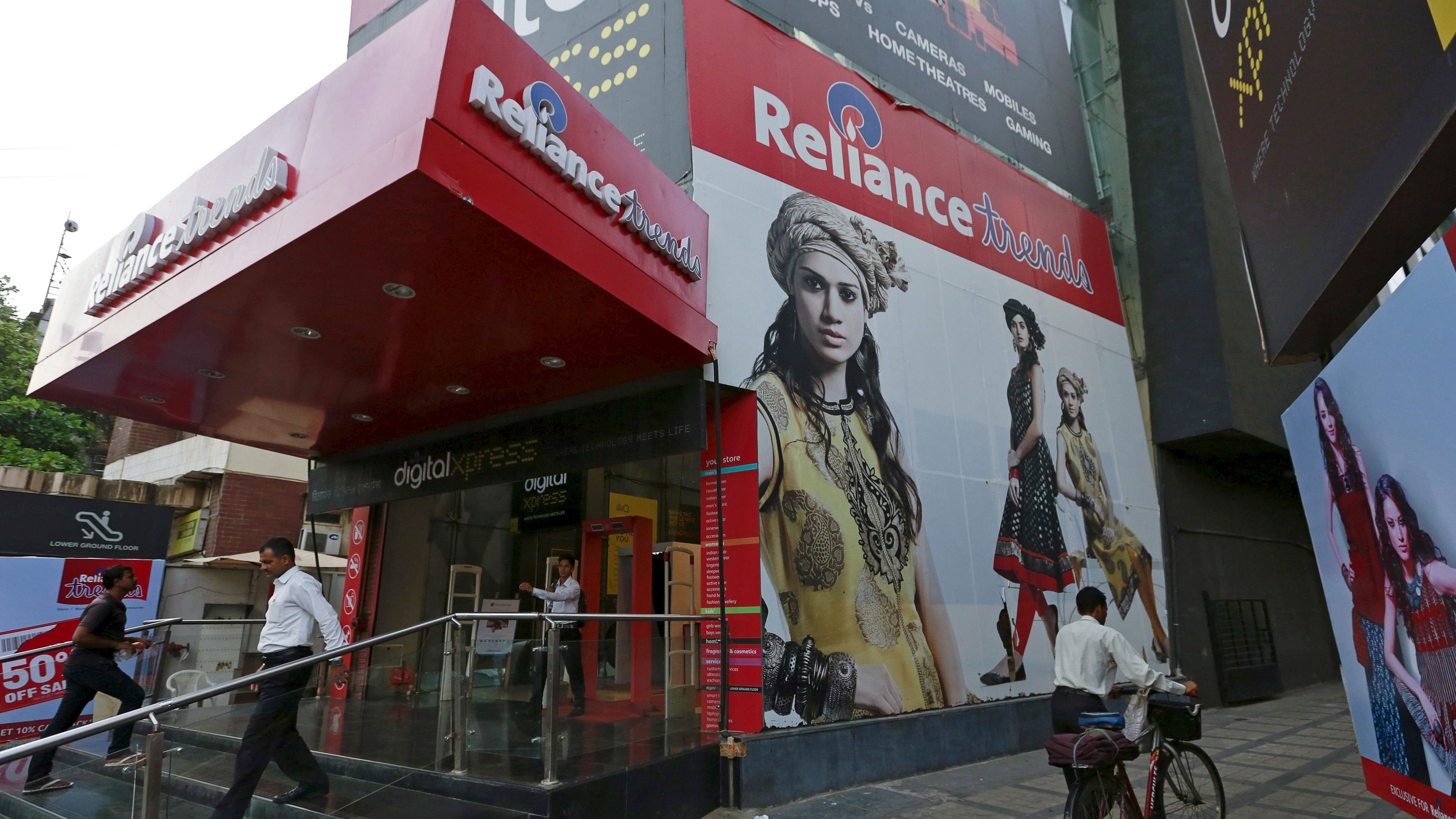 A man pushes a bicycle as others walk out of a Reliance Trends mall at a shopping district in Mumbai
