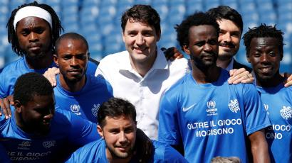 Canada's Prime Minster Justin Trudeau (C) poses with members of a refugees soccer team.