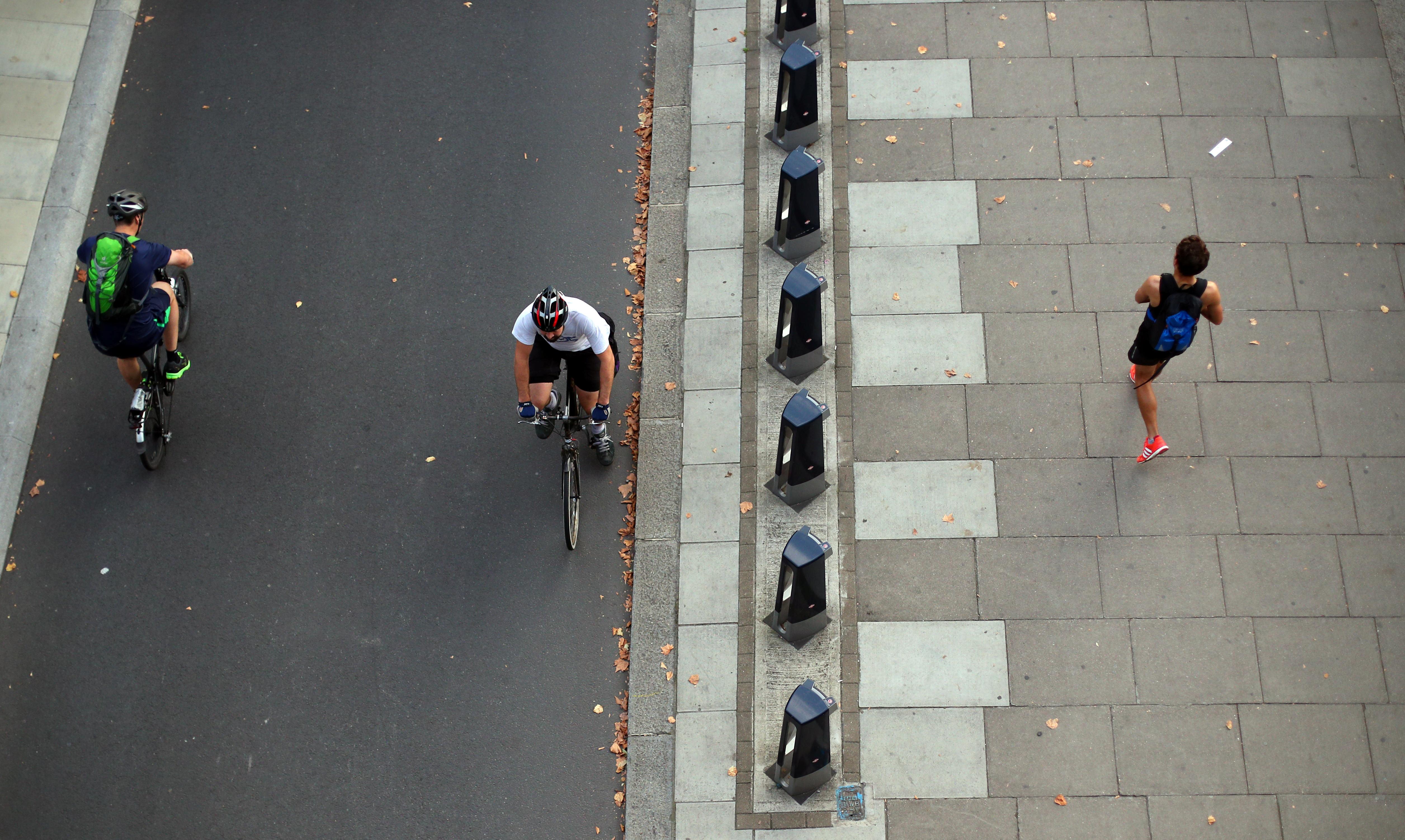 Les cyclistes passent un jogger le long de la digue pendant l'heure de pointe du matin dans le centre de Londres