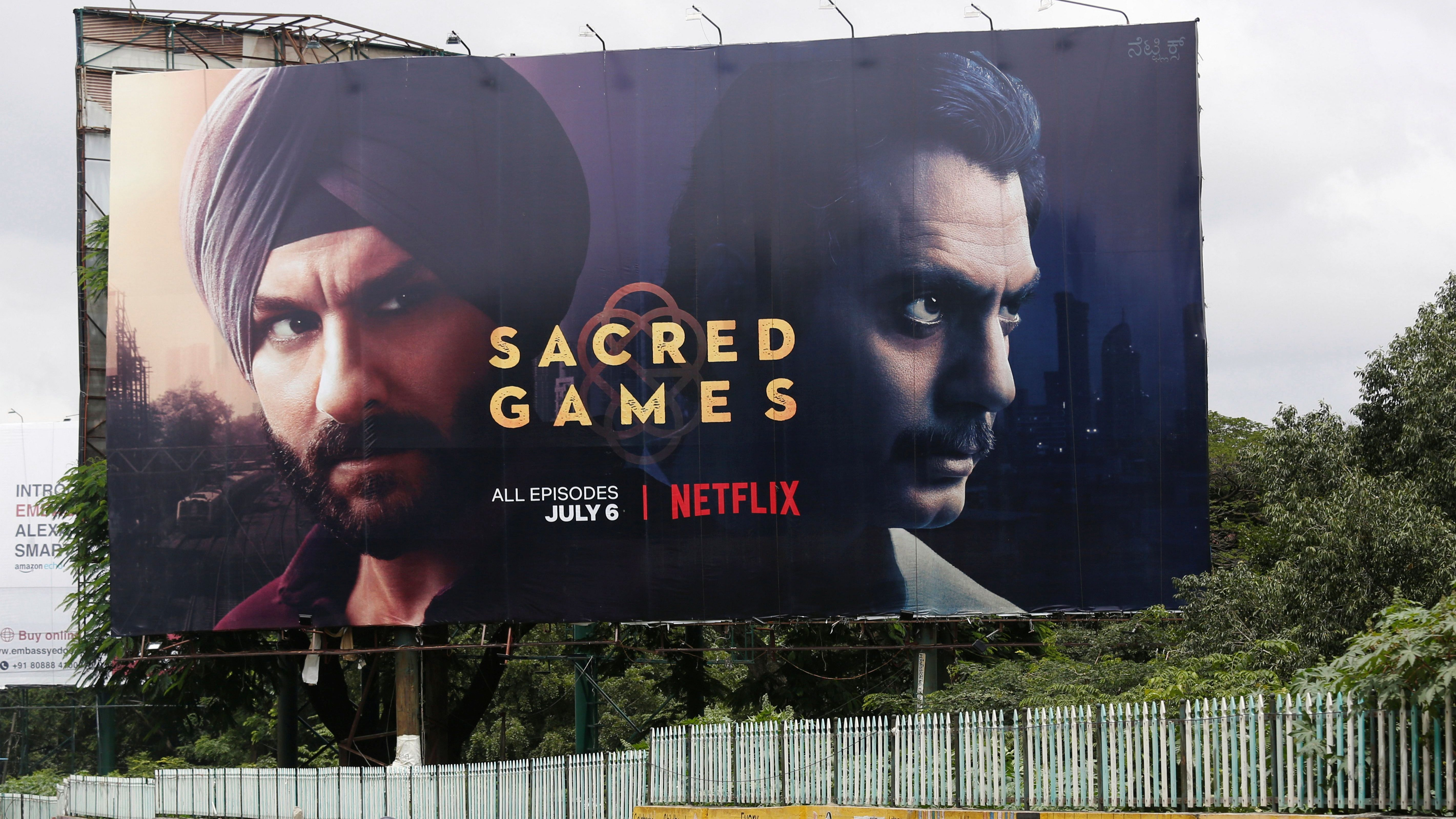 """A man rides his scooter past a hoardings of Netflix's new television series """"Sacred Games"""" in Bengaluru,"""