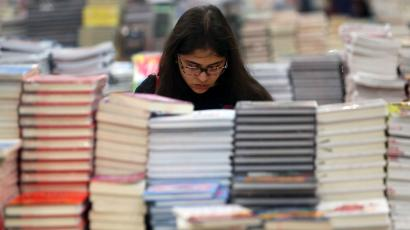 A visitor reads a book at the Big Bad Wolf Book Sale, which calls itself the world's biggest, hosted for the first time by Dubai