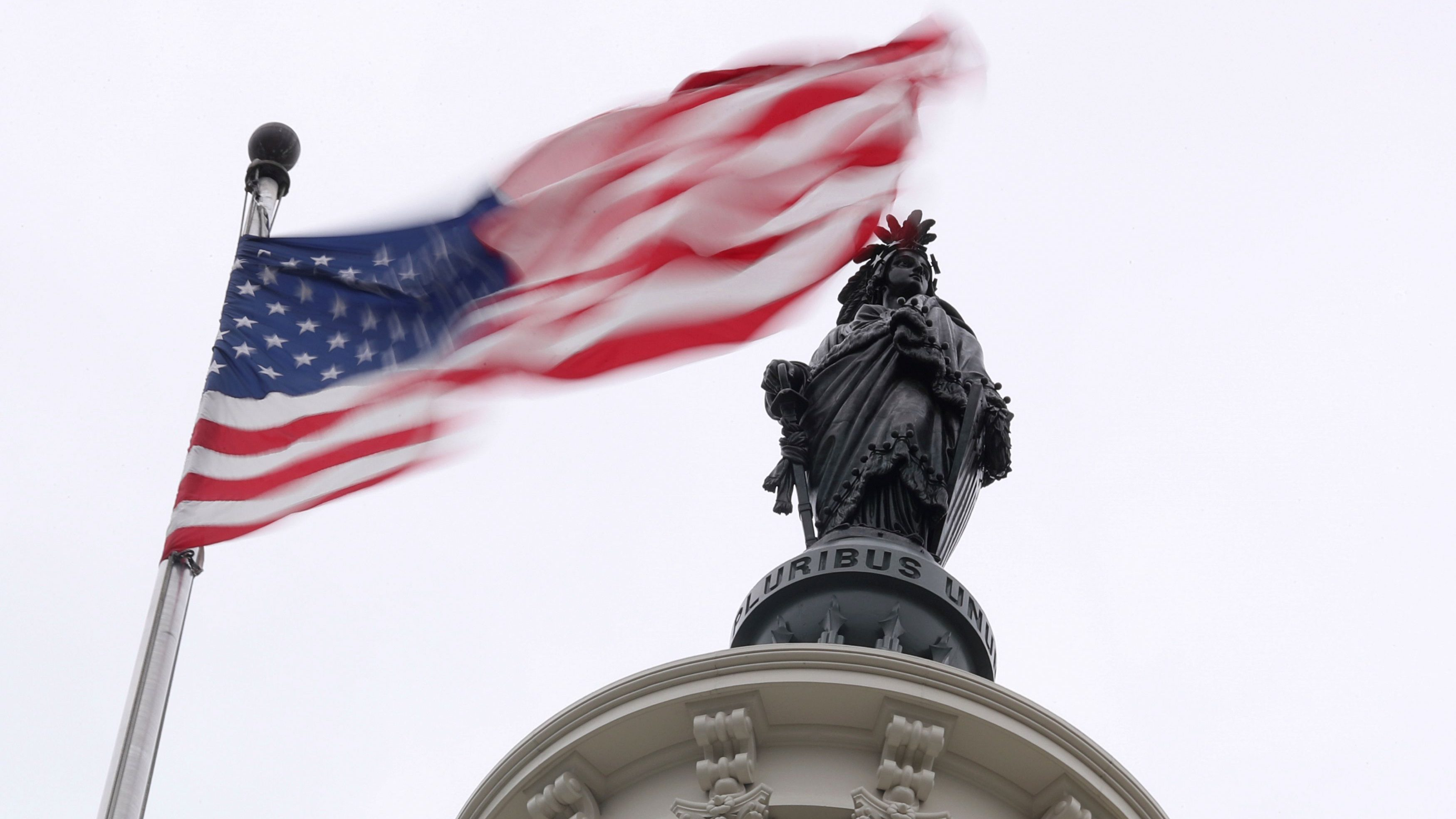 The U.S. flag flies near the Statue of Freedom atop the U.S. Capitol in Washington