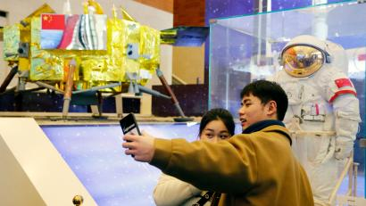 Chinese visitors take photos beside a Chinese space suit and a model of the Chang'e-3 lunar probe during an exhibition marking the 40th anniversary of China's reform and opening up at the National Museum of China in Beijing, China, 02 January 2019. China's Chang'e-4 lunar probe is expected to make the first-ever soft landing on the far side of the moon in coming days. Chinese lunar probe expected to land on moon in coming days, Beijing, China - 02 Jan 2019
