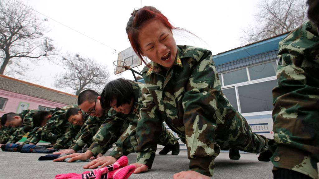 Students receive a group punishment during a military-style close-order drill class at the Qide Education Center in Beijing February 19, 2014. The Qide Education Center is a military-style boot camp which offers treatment for internet addiction. As growing numbers of young people in China immerse themselves in the cyber world, spending hours playing games online, worried parents are increasingly turning to boot camps to crush addiction. Military-style boot camps, designed to wean young people off their addiction to the internet, number as many as 250 in China alone. Picture taken February 19, 2014. REUTERS/Kim Kyung-Hoon (CHINA - Tags: SOCIETY)