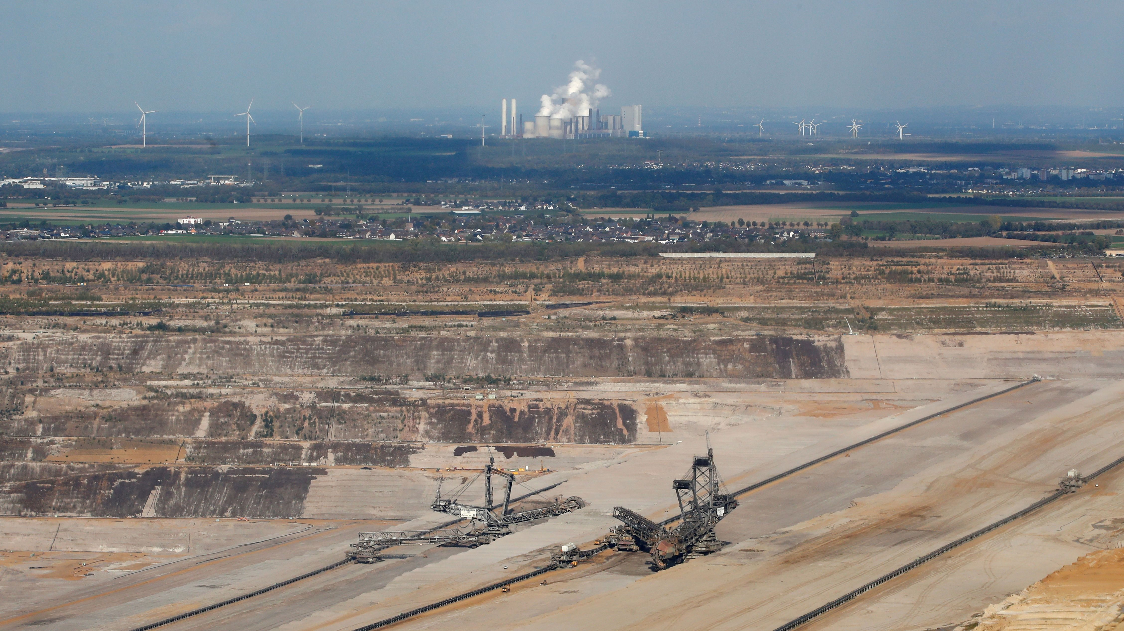 An aerial view of excavators in Hambach open-cast mine with RWE's brown coal power plant of Niederaussem in the backgroud, near the western German town of Kerpen-Buir west of Cologne, Germany, October 6, 2018.