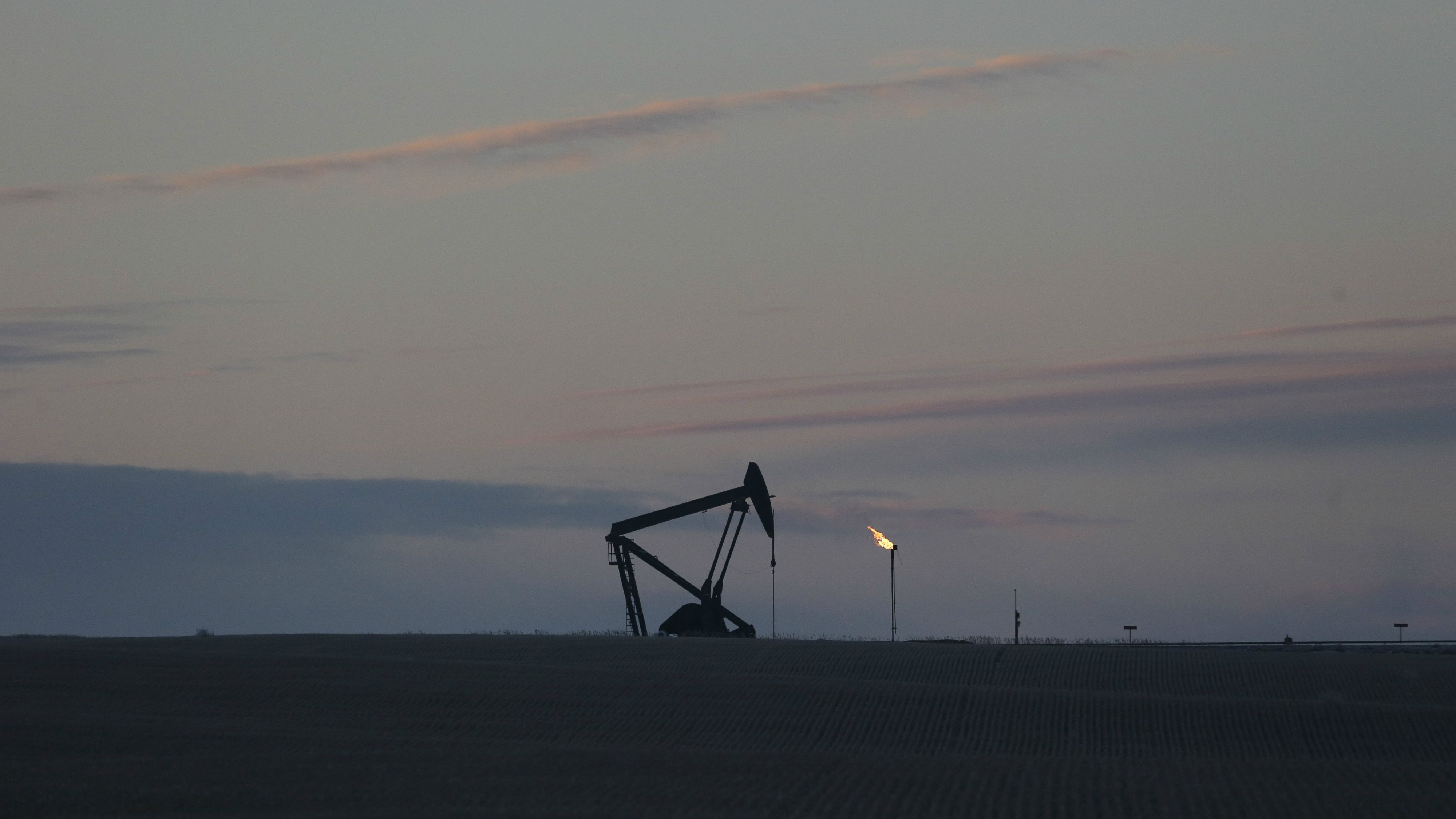 The sun begins to rise behind a pump jack and natural gas flare, Friday, Dec. 19, 2014, near Williston, N.D.