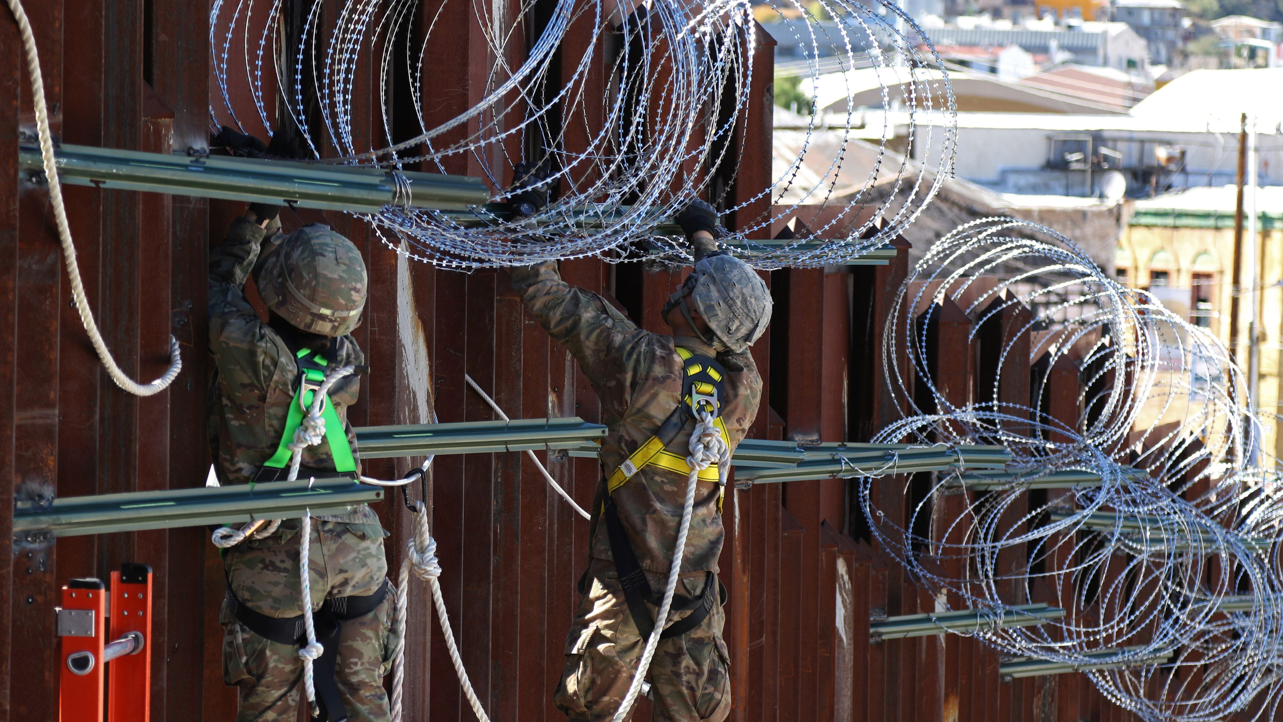US troops install concertina wire along border fence