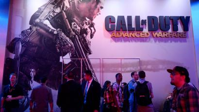 "Attendees walk pass a giant billboard promoting the new multiplayer action game ""Call of Duty: Advanced Warfare"" at the Activision booth during the 2014 Electronic Entertainment Expo,"