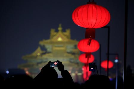 A visitor takes a picture of the Forbidden City decorated with red lanterns that is lit up during an event to celebrate the Chinese Lantern Festival on the last day of the lunar new year celebrations in Beijing, China February 19, 2019.