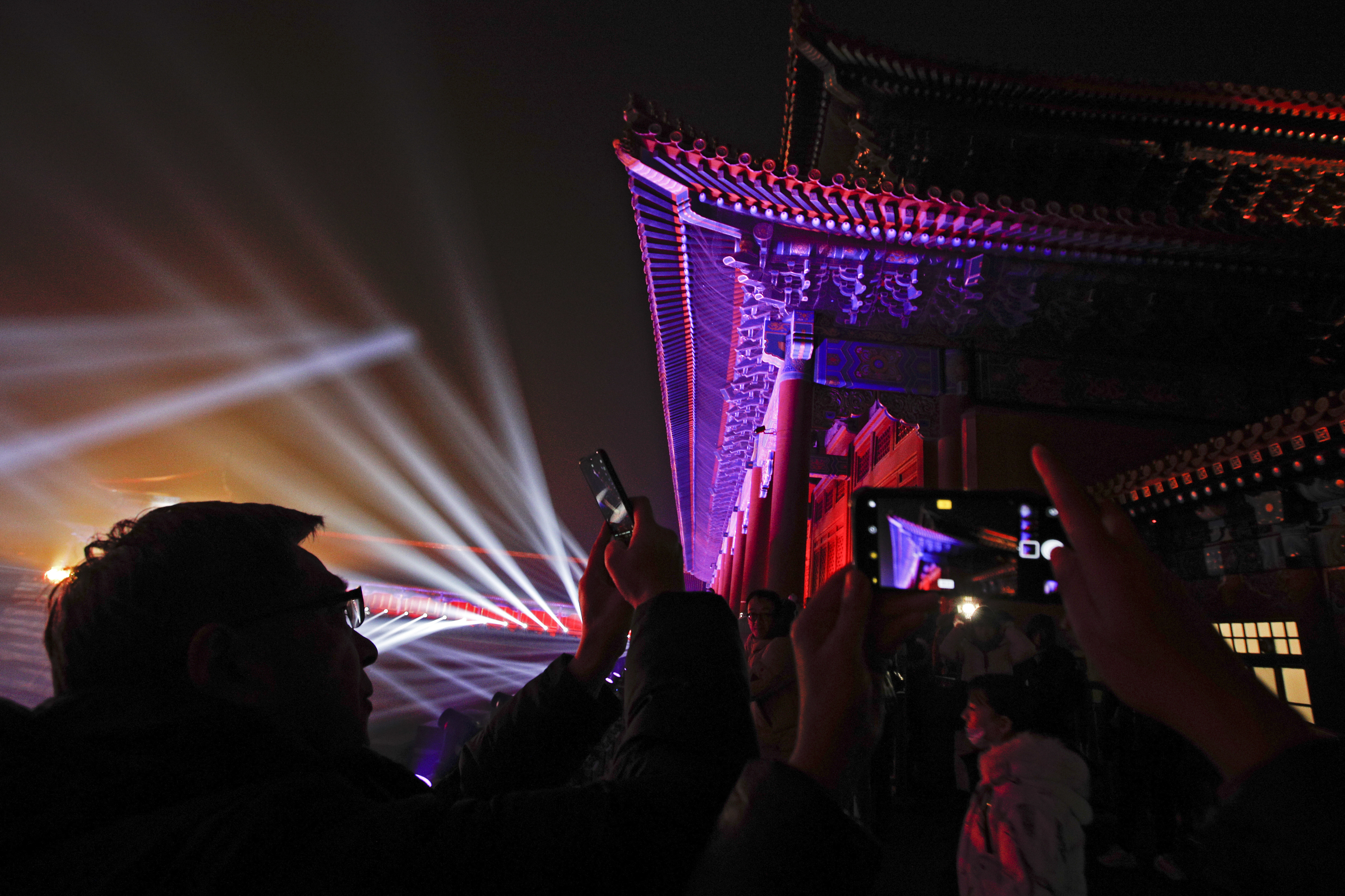 Visitors take souvenir photos of the Forbidden City illuminated with lights during the Lantern Festival in Beijing, Tuesday, Feb. 19, 2019. Beijing's Palace Museum was illuminated and opened for night visits to celebrate China's Lantern Festival. For the first time since it was established 94 years ago, the Palace Museum, also known as the Forbidden City, extended opening hours till nighttime and lit up part of its cultural relics buildings. (AP Photo/Andy Wong)