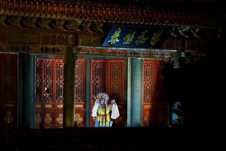 In this Tuesday, Feb. 19, 2019, photo, a Peking Opera artist performs in the Forbidden City which lit up by lights for the Lantern Festival in Beijing. China lit up the Forbidden City on Tuesday night, marking the end of 15 days of lunar new year celebrations. It was not a Lantern Festival the last emperor, who abdicated in 1912, would have recognized. There were lanterns, but those lucky enough to snag tickets saw a laser light show and historic buildings bathed in colorful lights. Others watched from outside the vast walled compound in Beijing, from where Ming and Qing dynasty emperors ruled for five centuries. (AP Photo/Andy Wong)