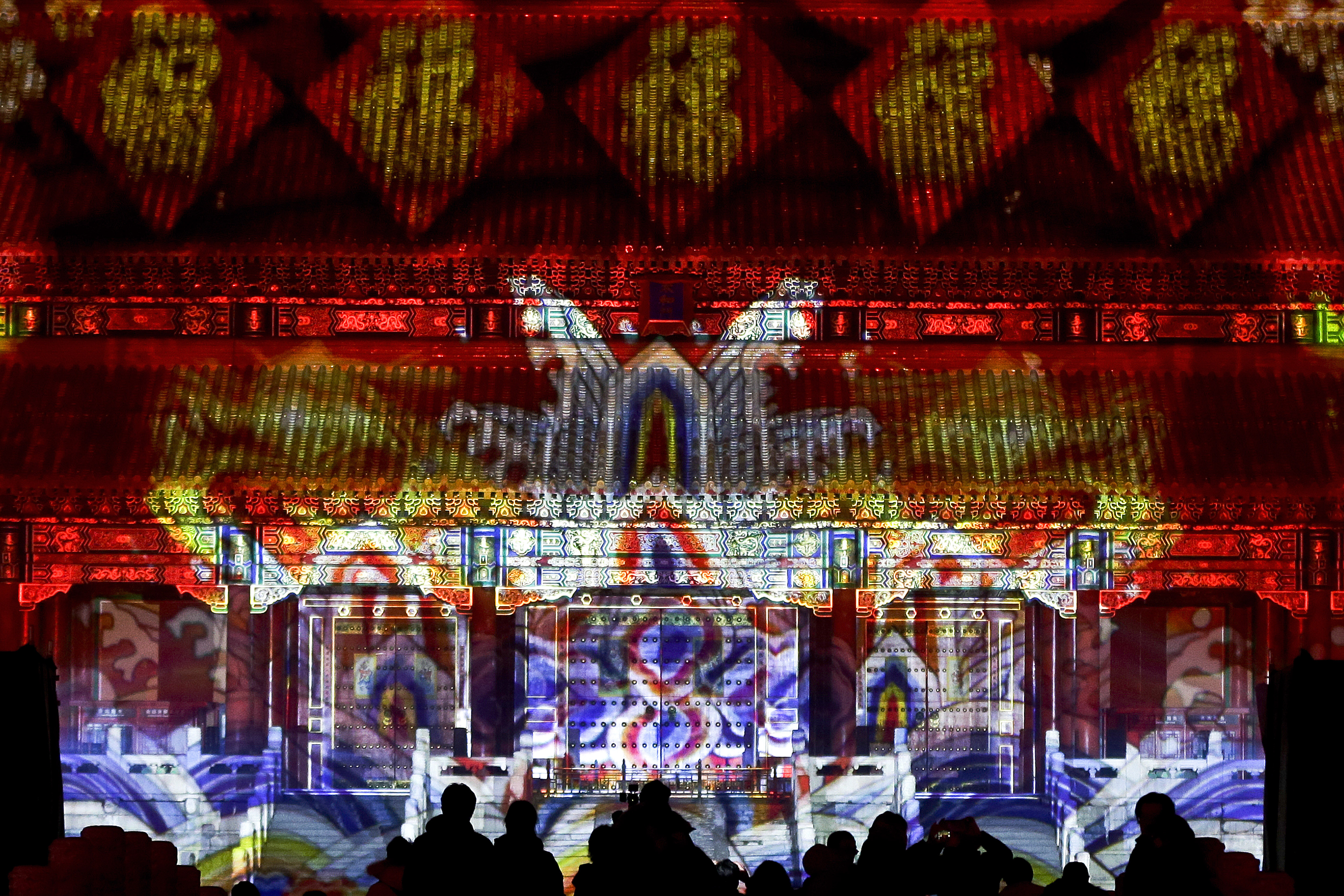 Visitors watch the Forbidden City is illuminated with colorful lights during the Lantern Festival in Beijing, Tuesday, Feb. 19, 2019. Beijing's Palace Museum was illuminated and opened for night visits to celebrate China's Lantern Festival. For the first time since it was established 94 years ago, the Palace Museum, also known as the Forbidden City, extended opening hours till nighttime and lit up part of its cultural relics buildings. (AP Photo/Andy Wong)