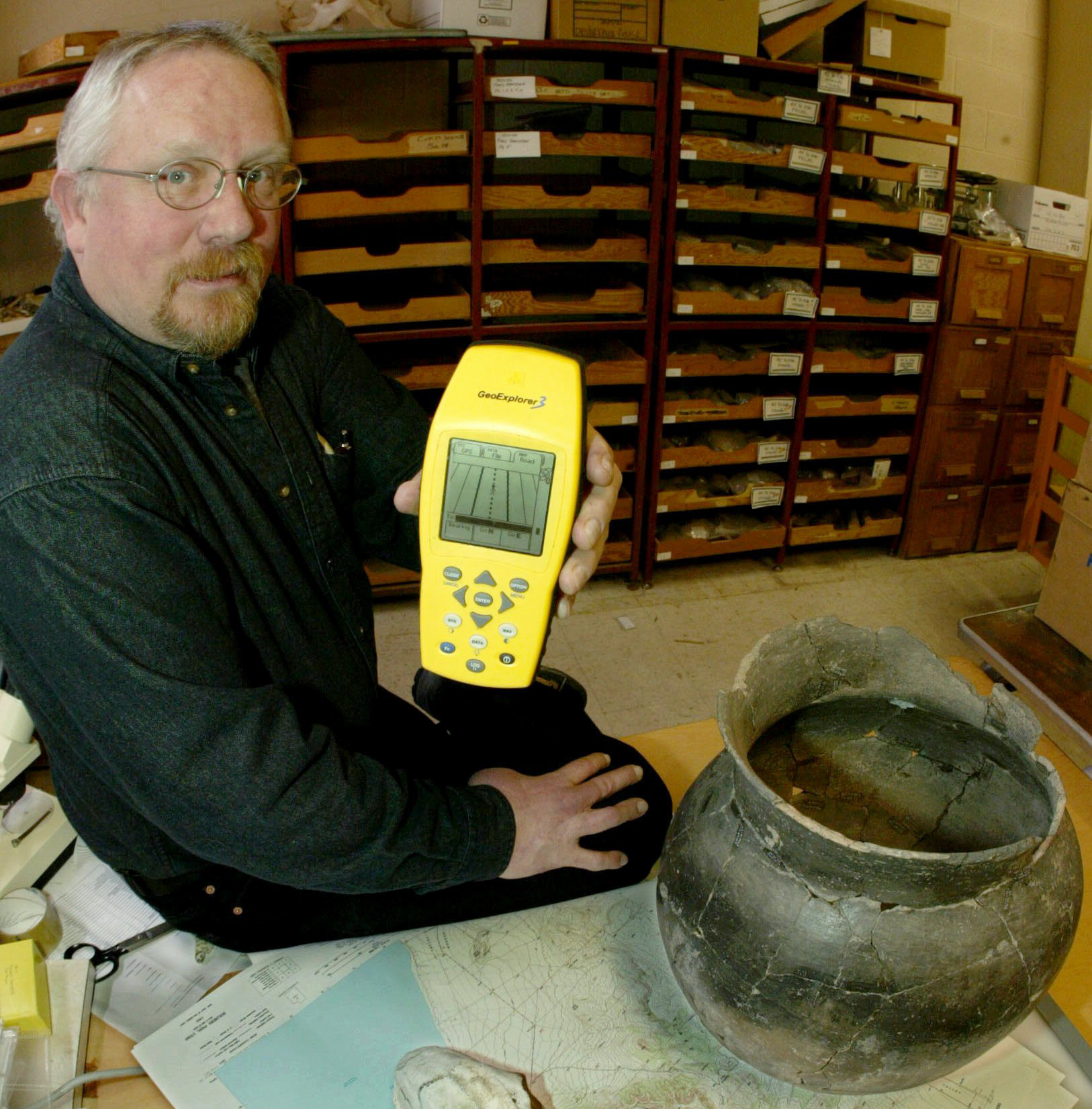 "** ADVANCE FOR WEEKEND OF APRIL 5-6 ** Kevin T. Jones Archaeologist for the State of Utah, poses with a GPS receiver while sitting next to a 1,000 year old Fremont Indian pot and other artifacts in his lab in Salt Lake City, Wednesday, April 2, 2003. There are concerns that with GPS coordinates and a map anyone can find artifacts that are normally hidden or hard to find, leaving ancient, priceless art vulnerable to what the Bureau of Land Management calls ""digital vandalism."""