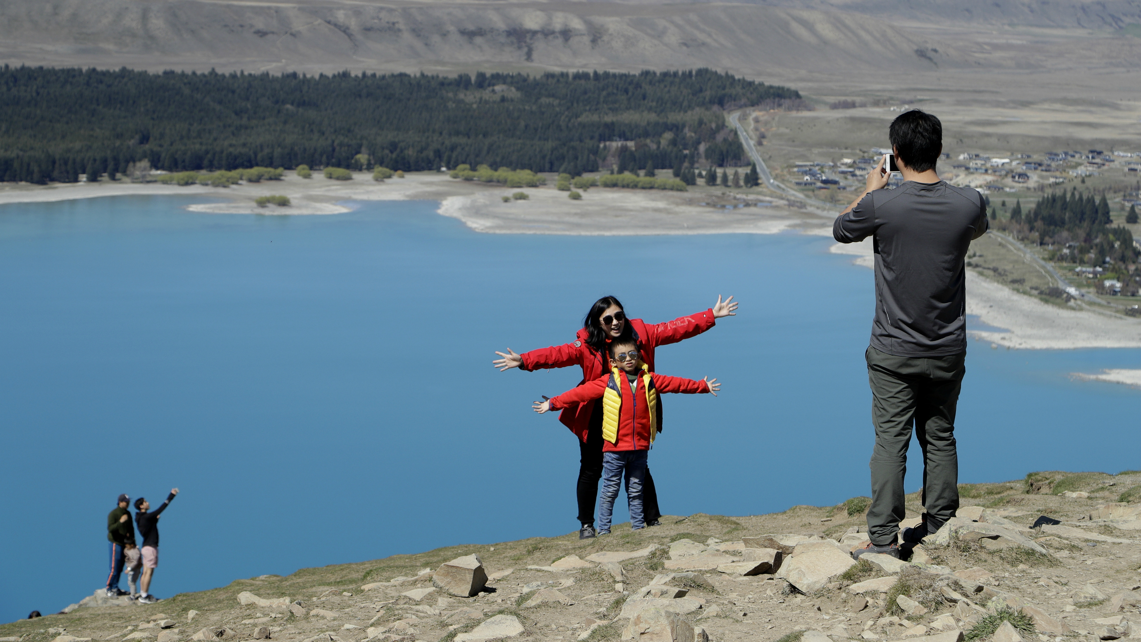 Tourists taking a picture at a lake in New Zealand.
