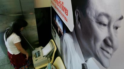 A reporter uses a fax near the portrait of ousted prime minister Thaksin Shinawatra displayed on the walls of the Thai Rak Thai party headquarter in Bangkok