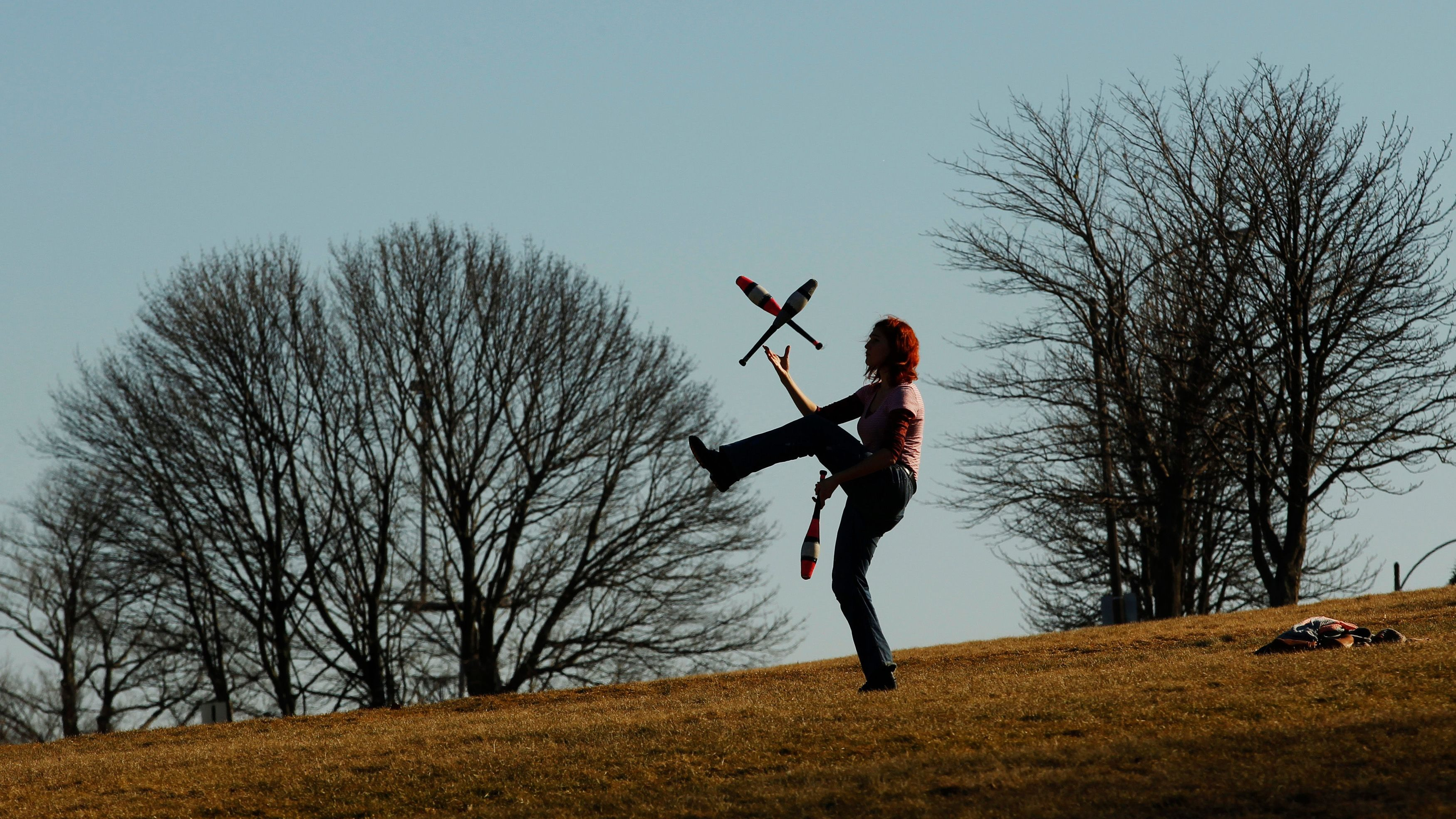Abbeth Russell juggles along the Eastern Promenade on an afternoon with mild temperatures in Portland