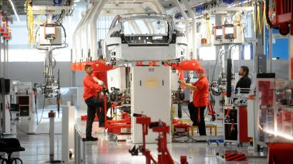 Tesla workers examine a Model S used for training and tool calibration at the company's factory in Fremont, California, June 22, 2012. Tesla began delivering the electric sedan to customers on June 22. REUTERS/Noah Berger (UNITED STATES) - TM3E86M1CK401