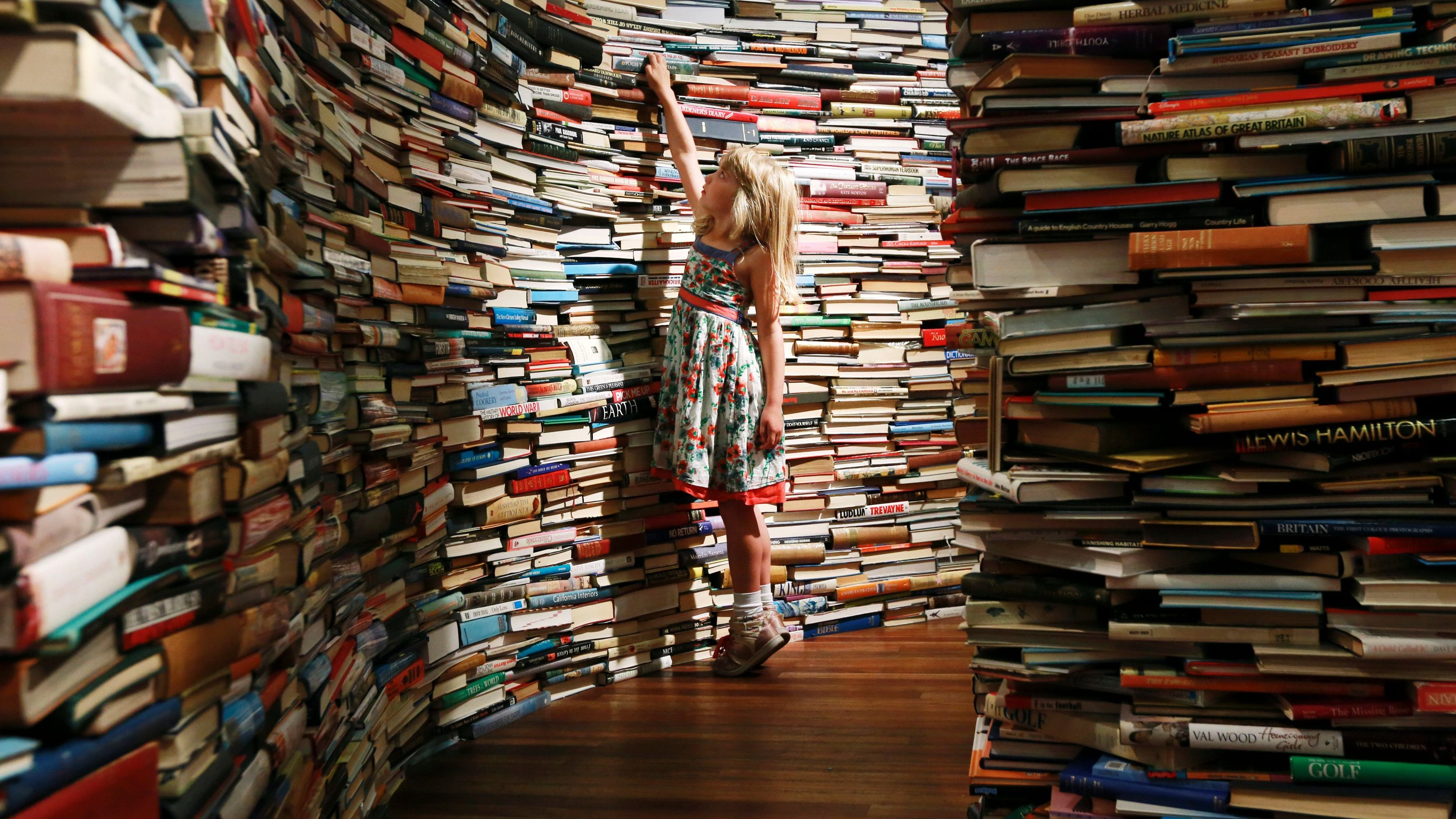 Leona, 7, poses inside a labyrinth installation made up of 250,000 books.
