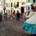 A woman dressed in a traditional Bahia costume stands under decorations for the 2014 World Cup at Pelourinho in Salvador, June 14, 2014. REUTERS/Marcos Brindicci (BRAZIL - Tags: SPORT SOCCER WORLD CUP SOCIETY) - TB3EA6E1PMMU4