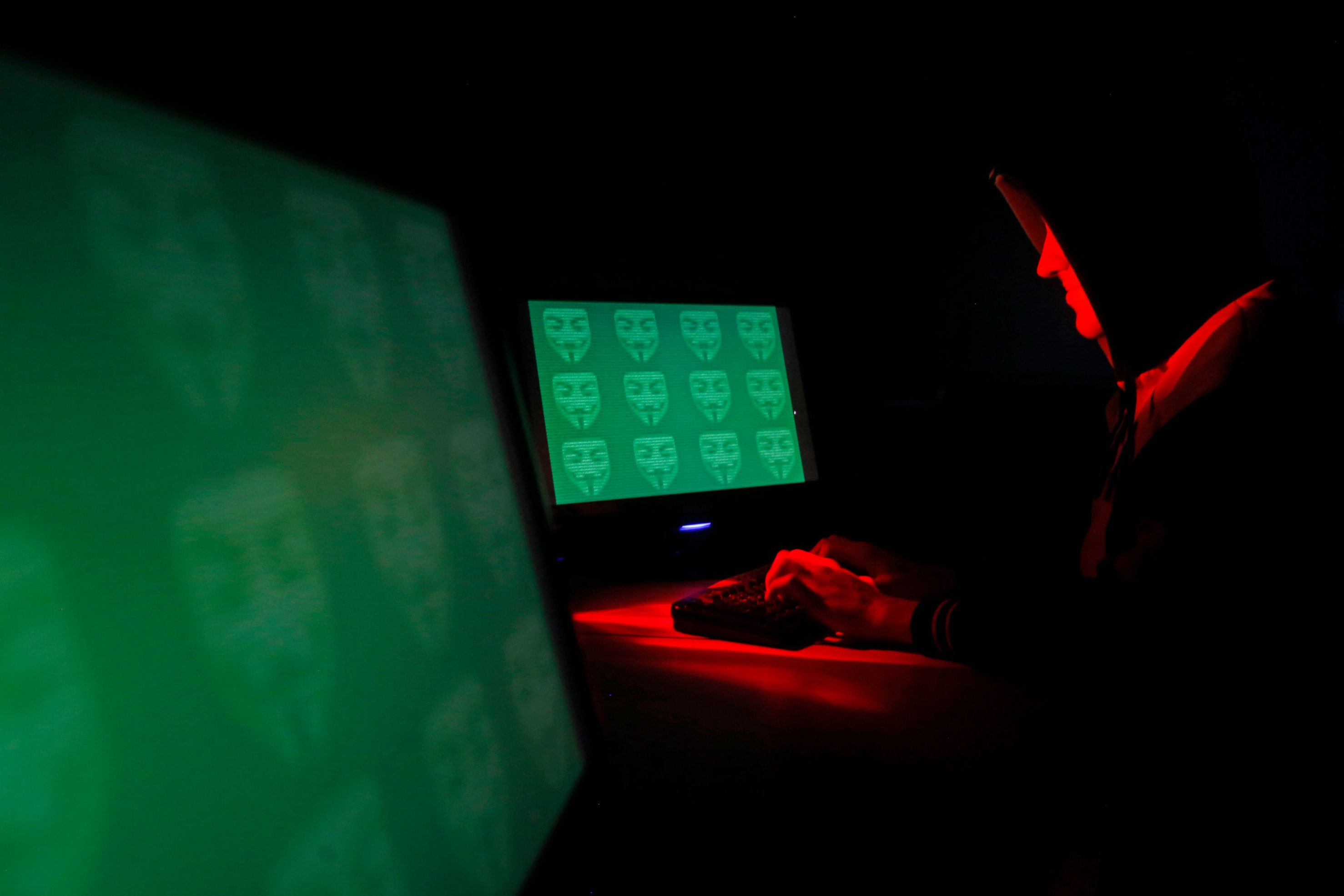 Man poses in front of on a display showing the word 'cyber' in binary code, in this picture illustration taken in Zenica