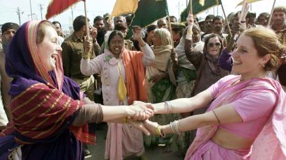 FOREIGN TOURISTS DRESSED IN TRADITIONAL SARIS DANCE WITH INDIANS DURING THE MAHA KUMBH MELA FESTIVAL ...