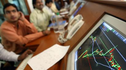 Indian brokers watch a screen of prices
