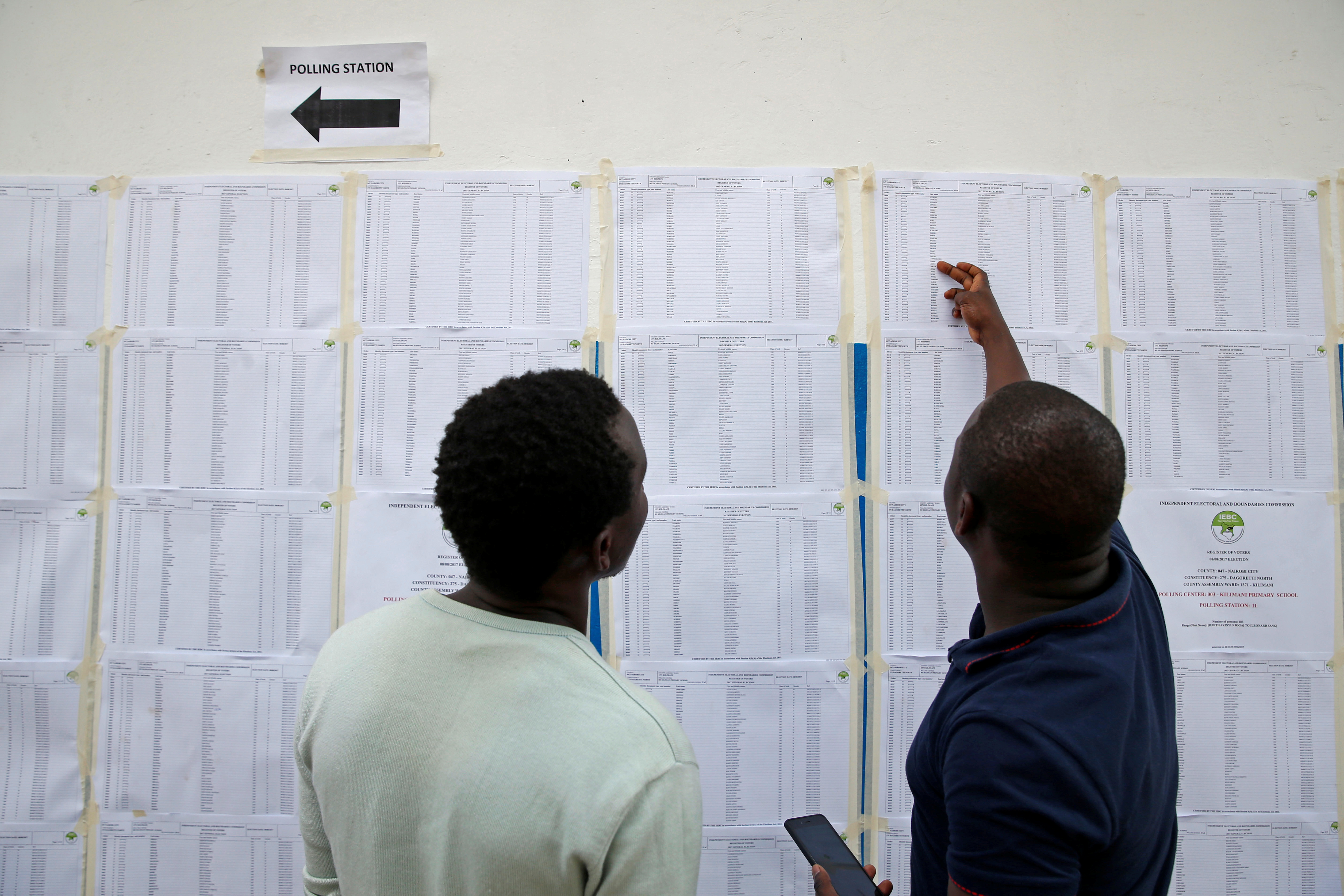 Voters search for their names on an electorate list near a polling station ahead of the presidential election, in Nairobi, Kenya August 7, 2017.