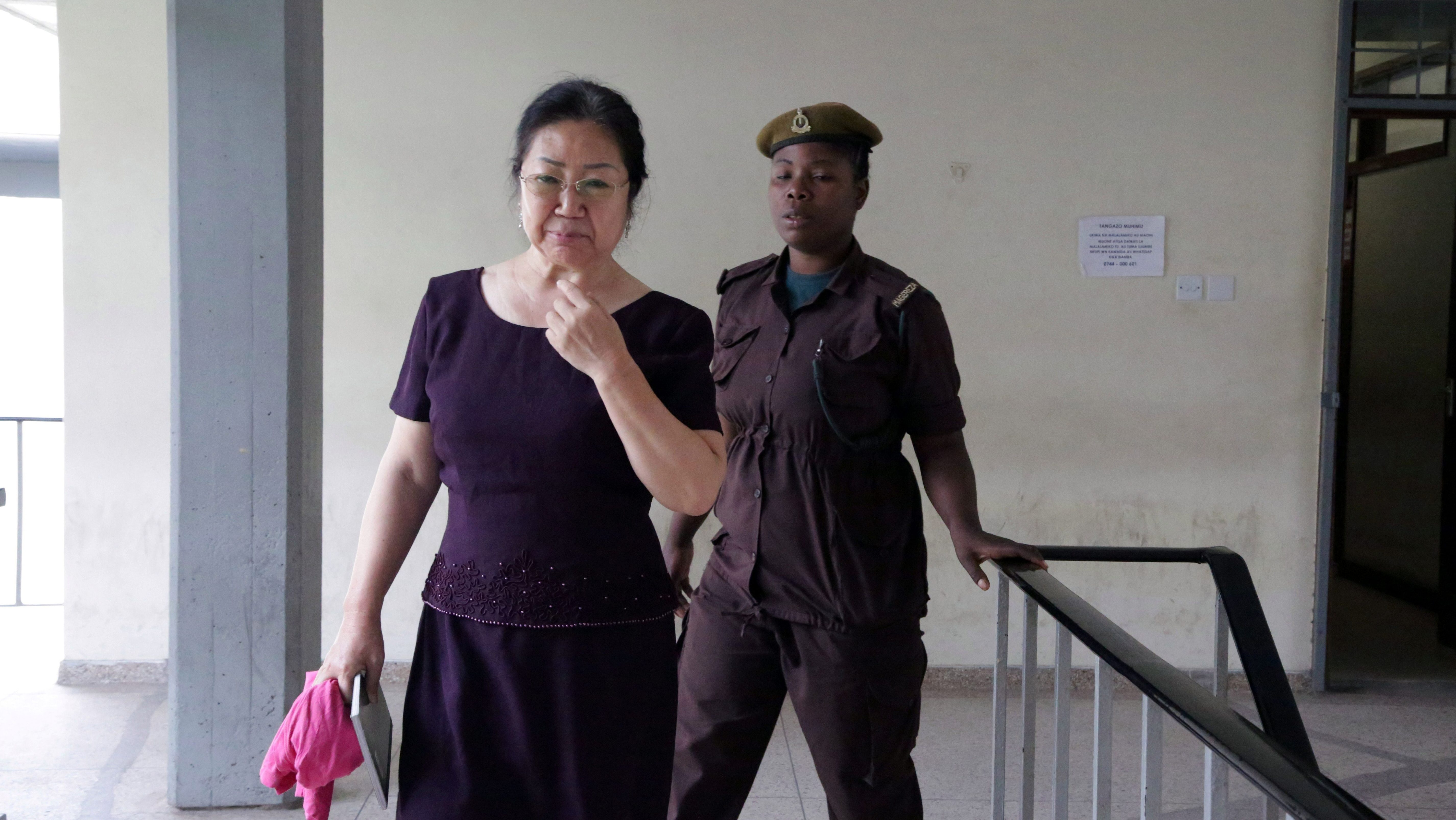 """Chinese businesswoman Yang Feng Glan, dubbed the """"Ivory Queen"""", is escorted by a prison warden at the Kisutu Resident Magistrate Court in Dar es Salaam, Tanzania September 25, 2017."""