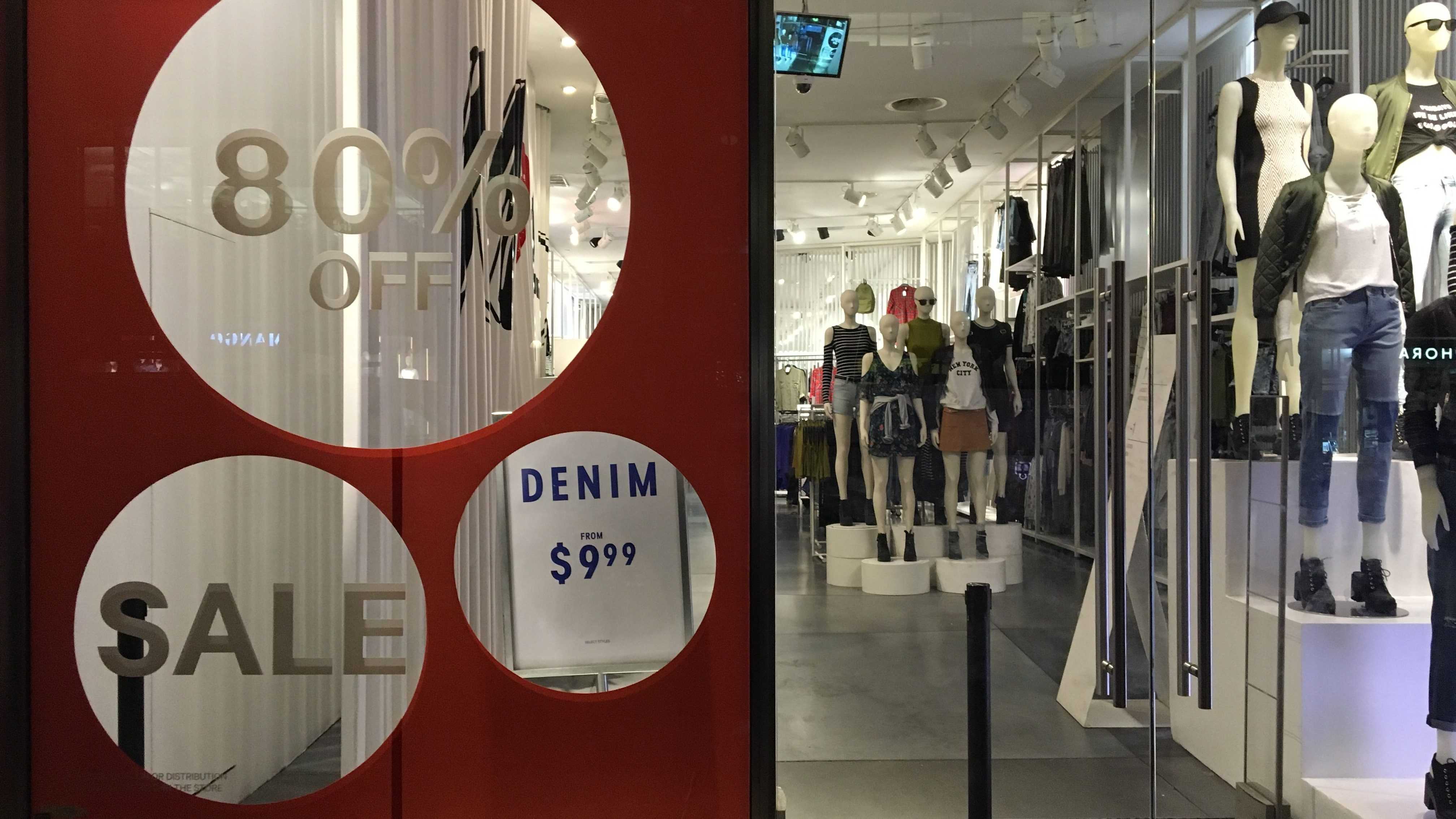 An H&M store has sale signs in the window in New York City, U.S., August 11, 2016. Picture taken August 11, 2016. U.S. retail sales were unexpectedly flat in July as Americans cut back on purchases of clothing and other goods, pointing to a moderation in consumer spending that could temper expectations of an acceleration in economic growth in the third quarter. REUTERS/Joe White - TM3EC8C0TK901