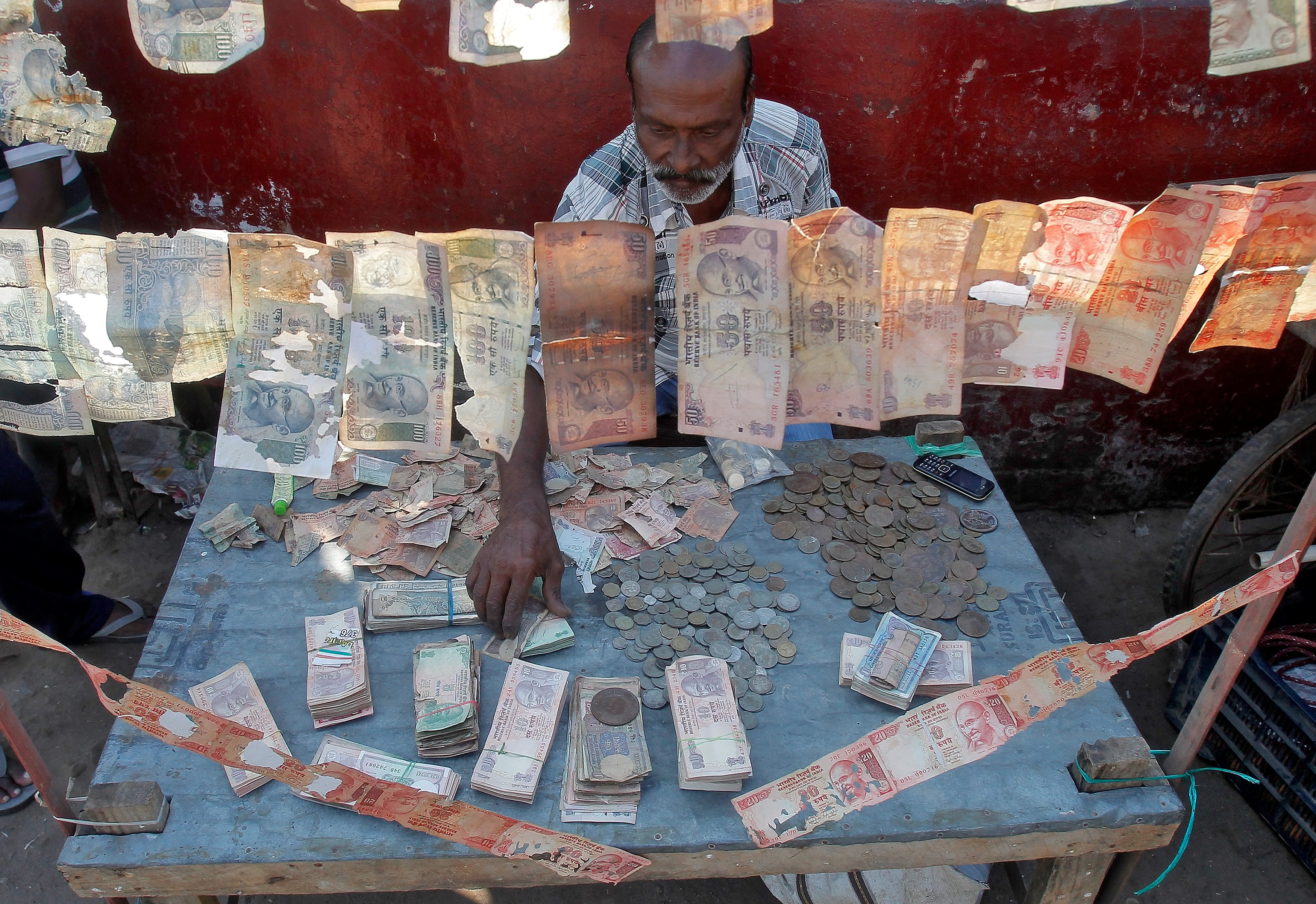 A roadside currency exchange vendor sorts Indian currency notes at his stall in Agartala