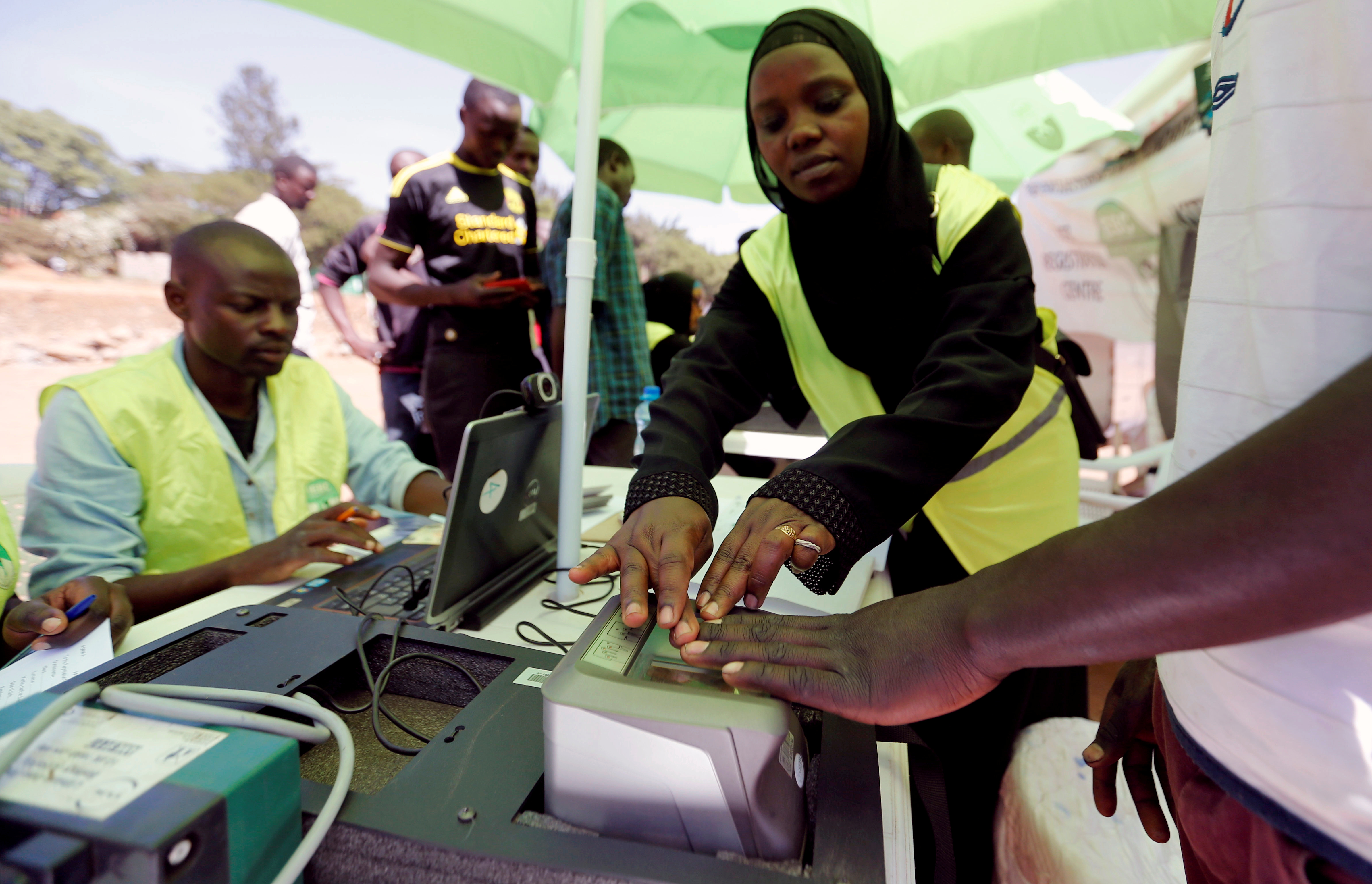 Officials from the Independent Electoral and Boundaries Commission (IEBC) records finger prints of a man as they collect data from the electorate during the launch of the 2017 general elections voter registration exercise within Kibera slums in Kenya's capital Nairobi, January 16, 2017.