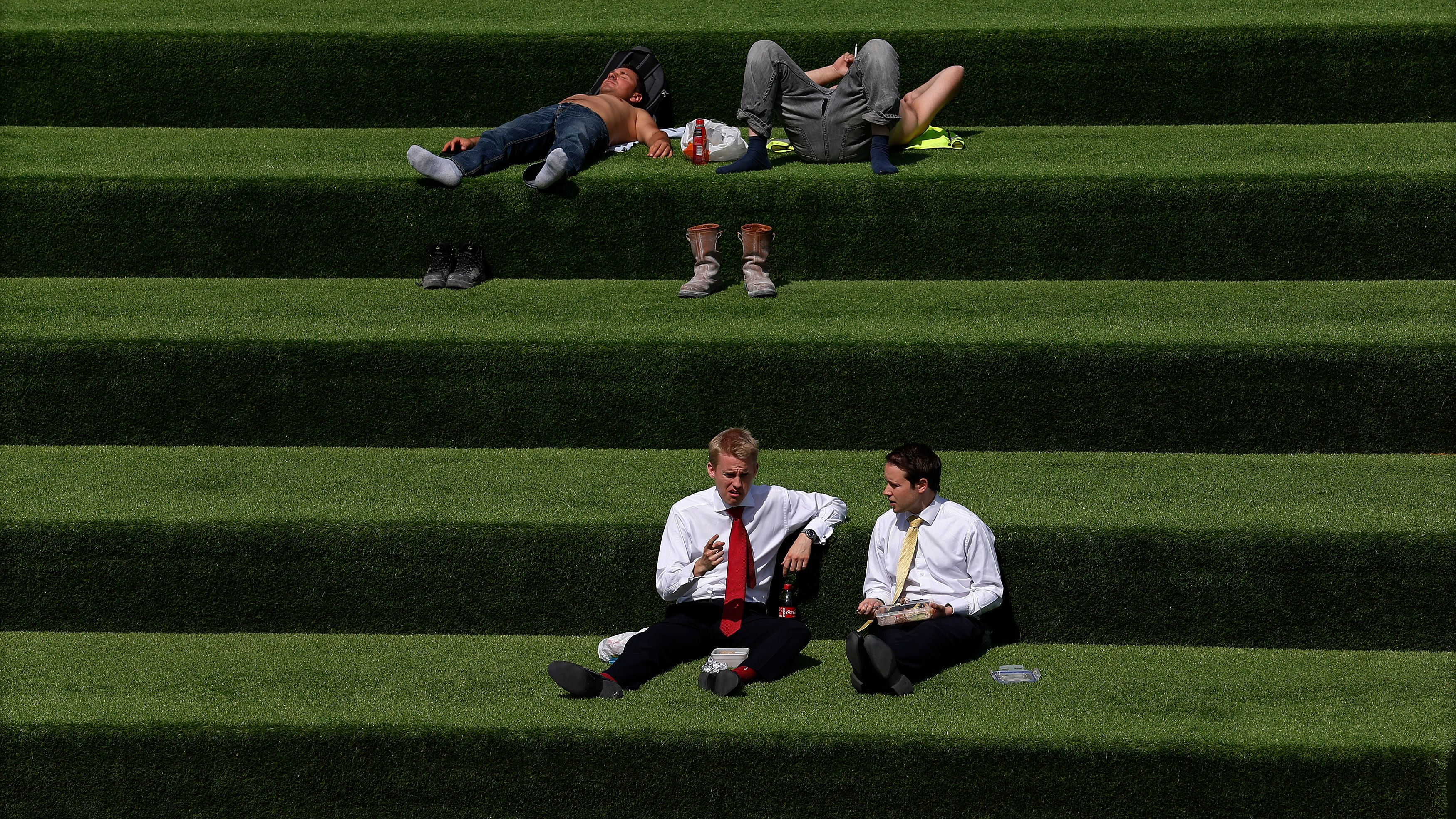 Men eat lunch and relax on a stairway covered in artificial grass near St. Pancras Station in London