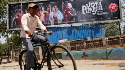 A man rides his bicycle past a poster of the movie