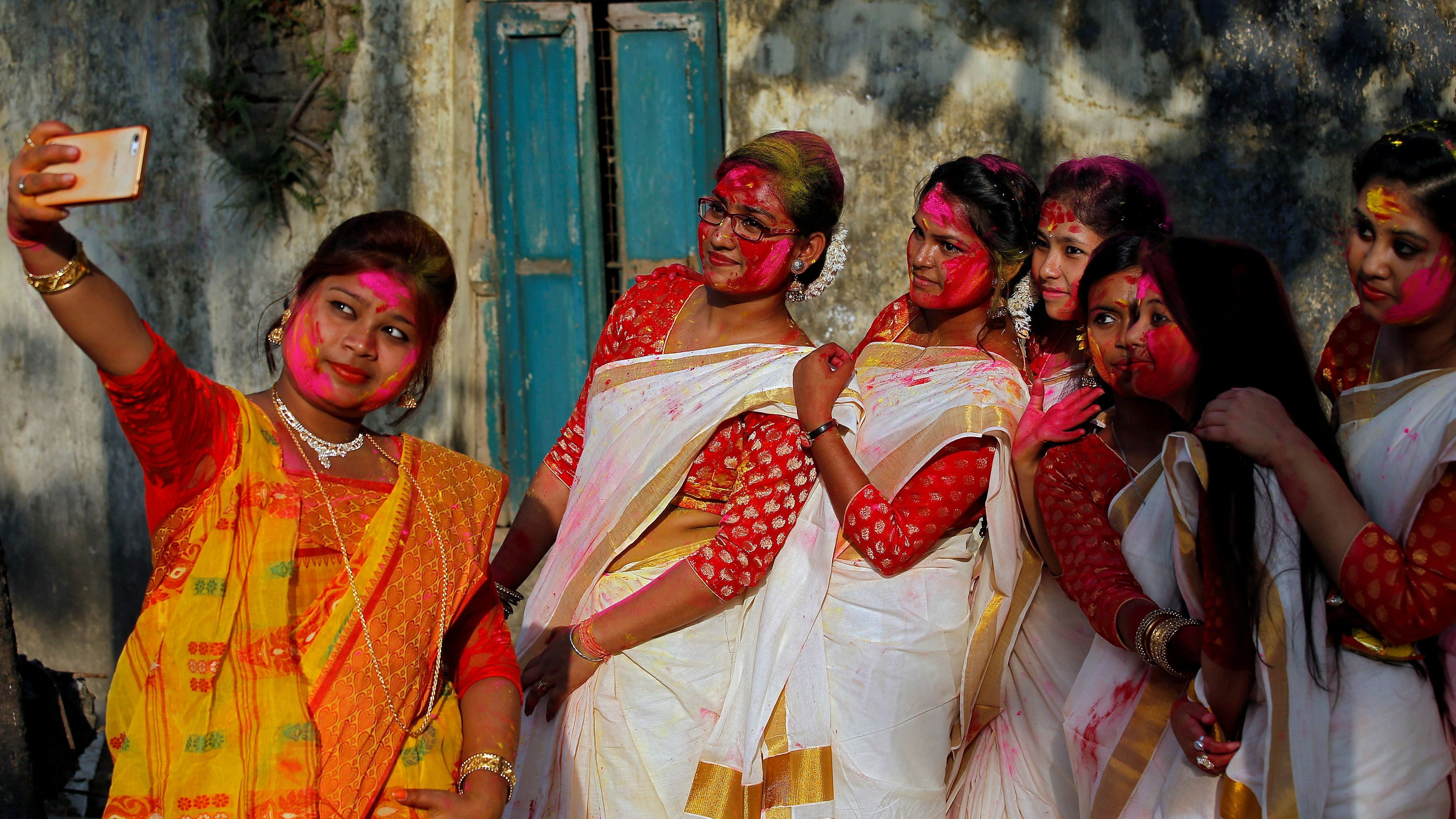 Students of Rabindra Bharati University, with their faces smeared in coloured powder, take a selfie during celebrations for Holi inside the university campus in Kolkata