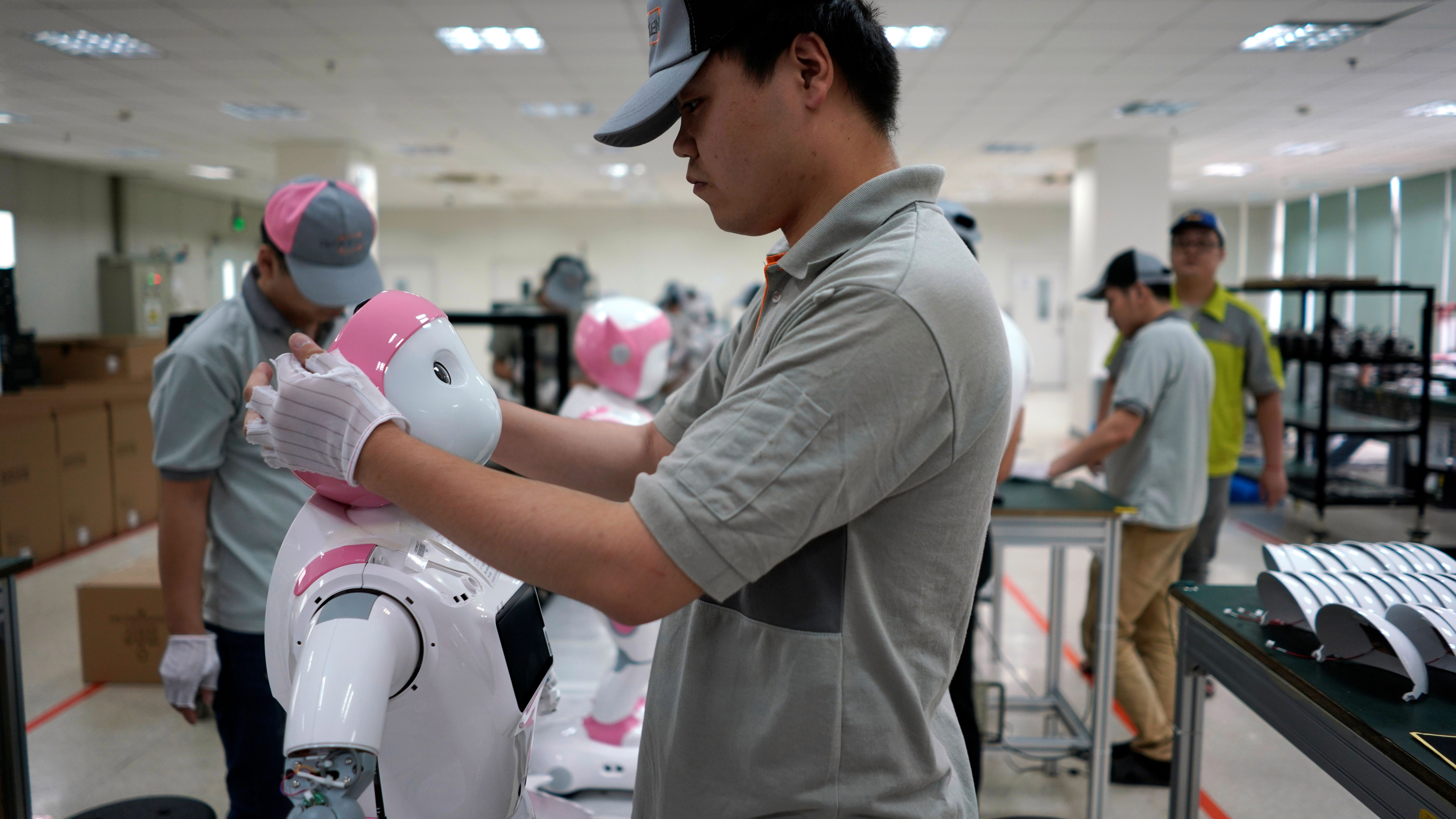 A worker puts finishing touches to an iPal social robot, designed by AvatarMind, at an assembly plant in Suzhou, Jiangsu province, China July 4, 2018. Designed to offer education, care and companionship to children and the elderly, the 3.5-feet tall humanoid robots come in two genders and can tell stories, take photos and deliver educational or promotional content.
