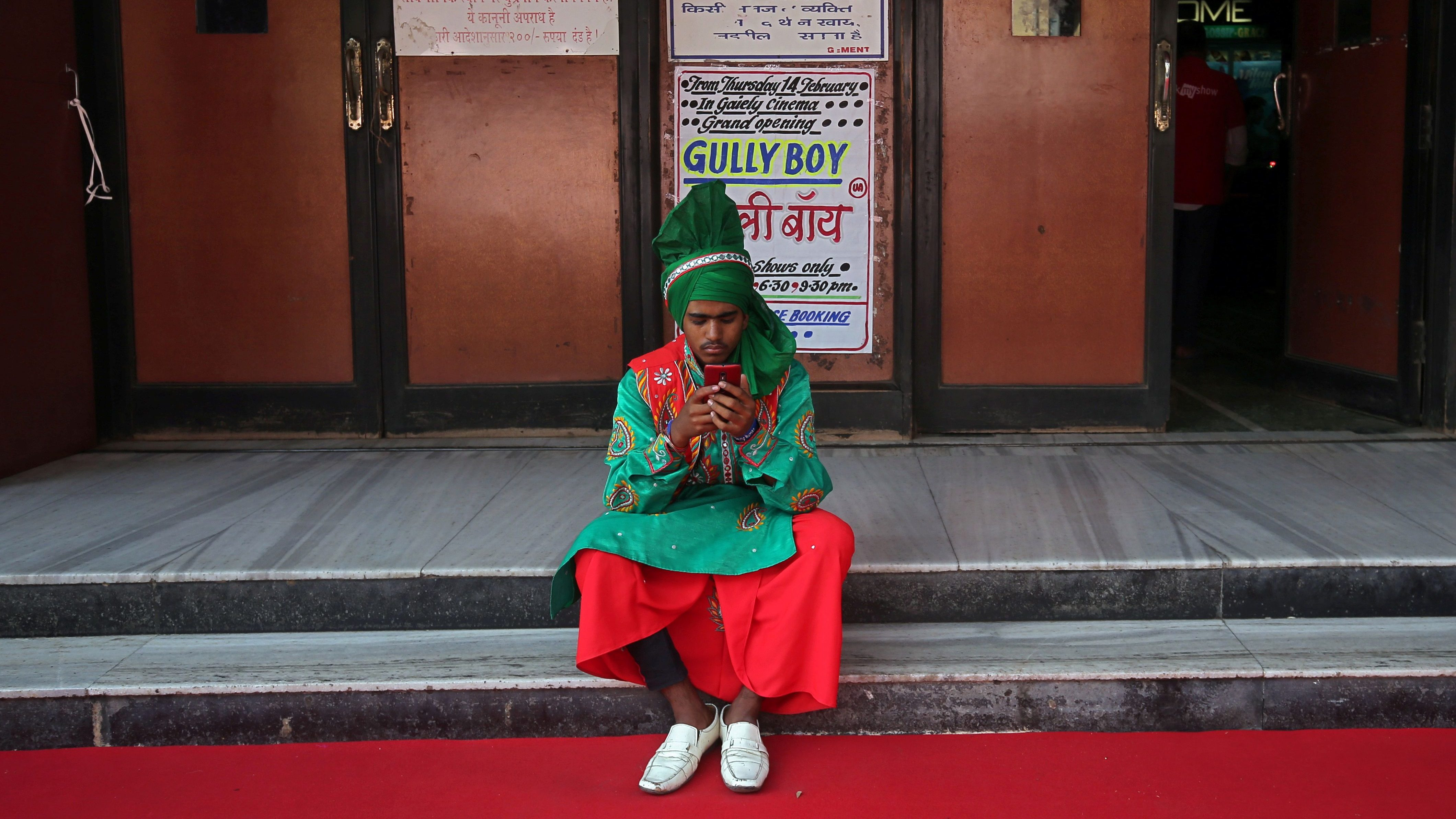A man wearing traditional attire checks his mobile phone as he waits to perform before the launch of the trailer of a Bollywood movie outside a cinema in Mumbai