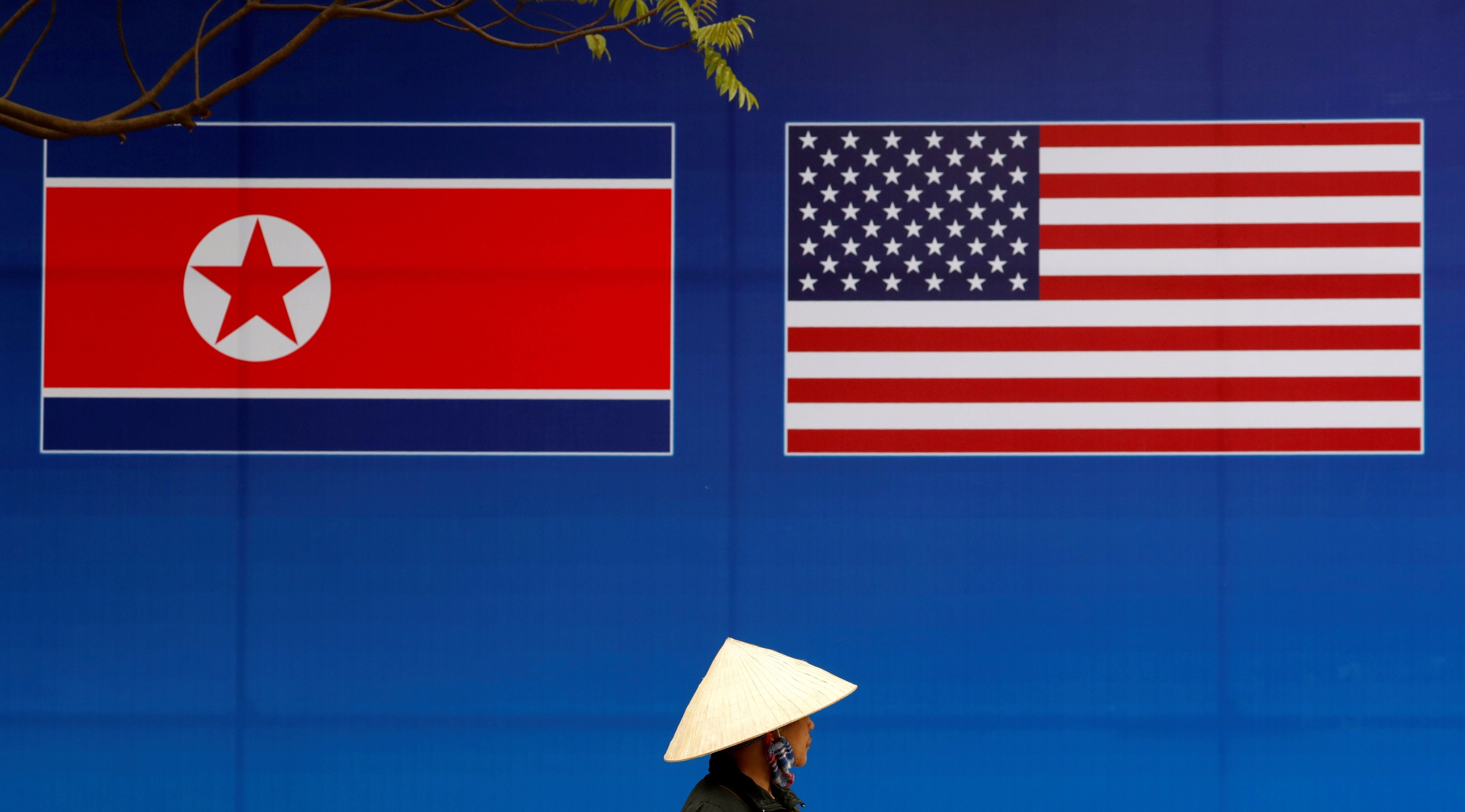 A person walks past a banner showing North Korean and U.S. flags ahead of the North Korea-U.S. summit in Hanoi, Vietnam