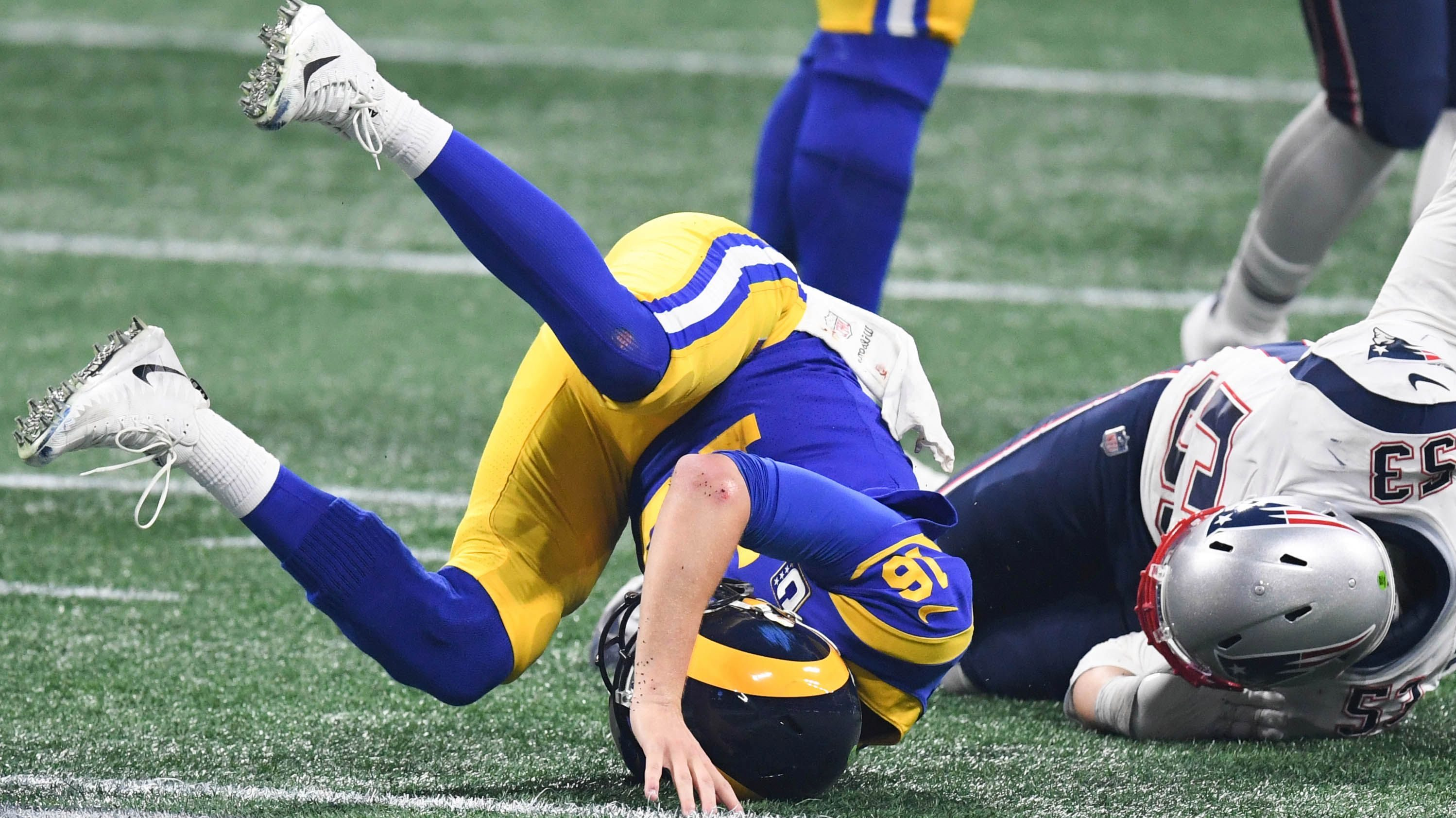 Los Angeles Rams quarterback Jared Goff (16) rolls over after a tackle by New England Patriots middle linebacker Kyle Van Noy (53) during the fourth quarter in Super Bowl LIII at Mercedes-Benz Stadium.