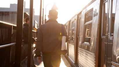 A commuter walks to board a subway train in the Brooklyn borough of New York City