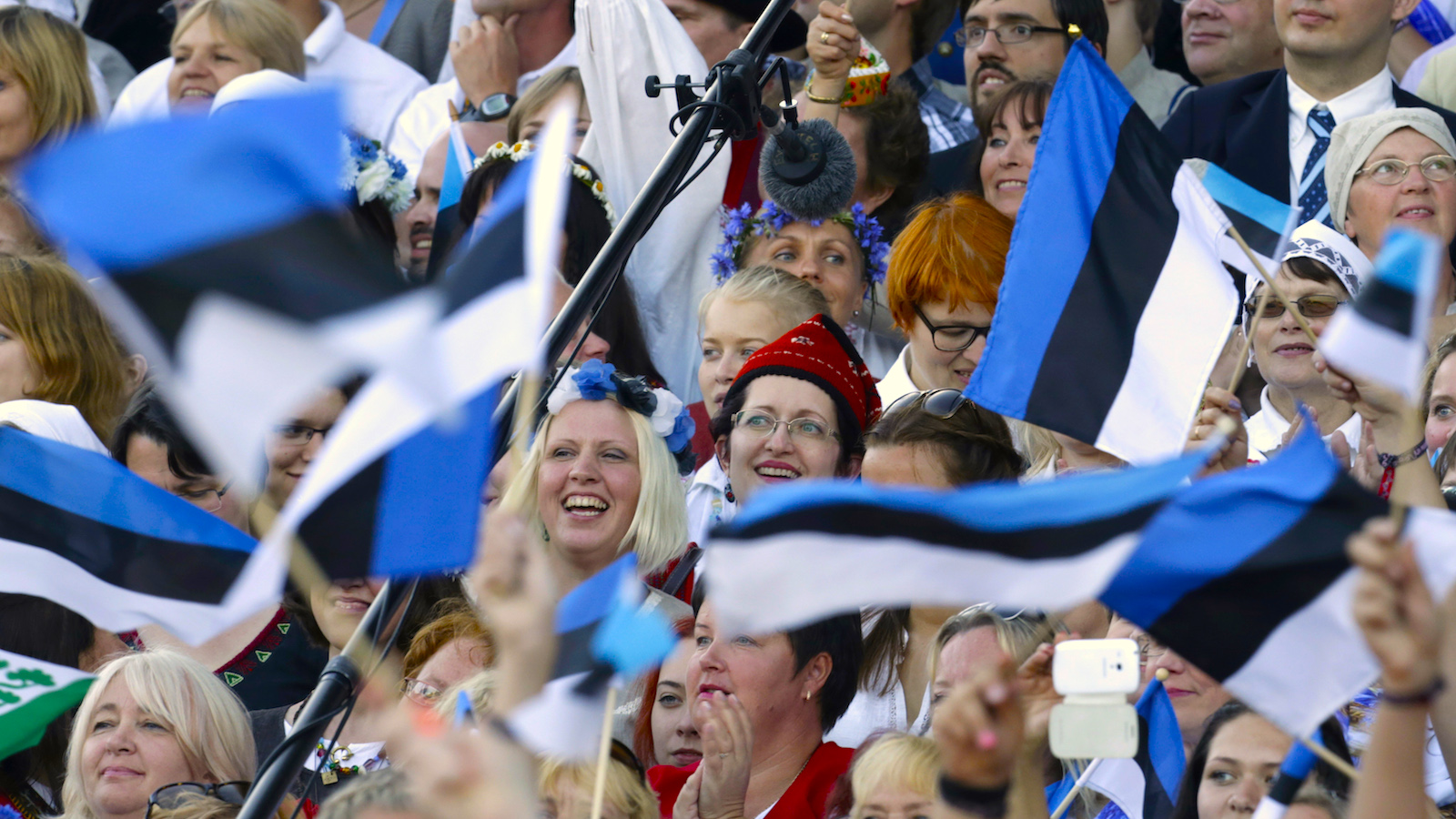 Singers wave Estonia's flags as they perform during the Song and Dance Celebration in Tallinn