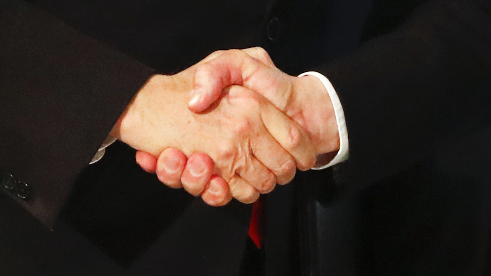two white men in suits shaking hands