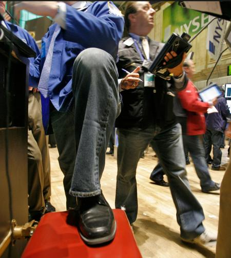 Traders wear blue jeans as they work on the floor of the New York Stock Exchange Friday, Aug. 21, 2009. Gap Inc., who celebrates their 40th anniversary, provided the jeans to traders who were allowed to wear them on the trading floor for the first time in the market's history.(AP Photo/Richard Drew)
