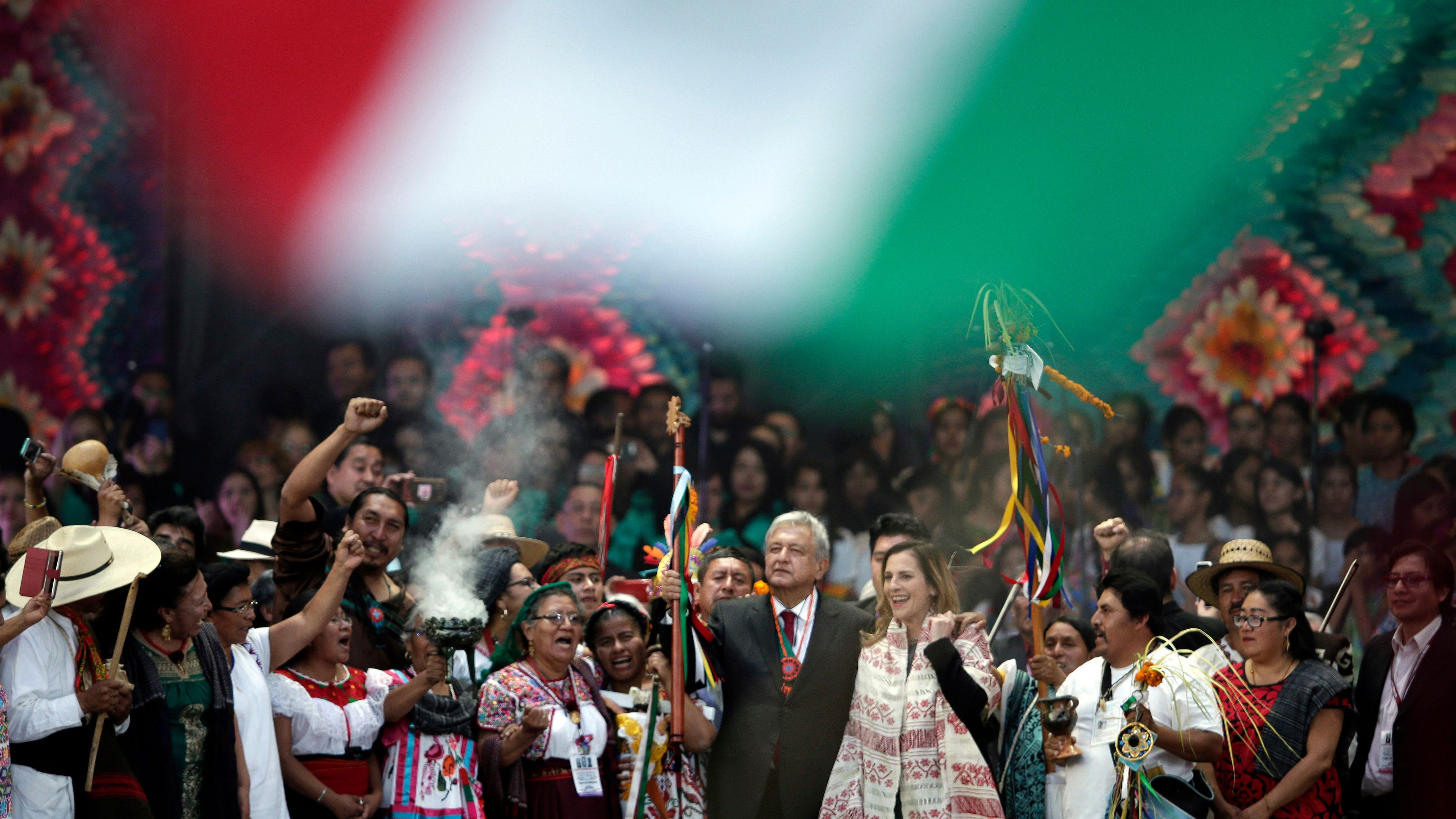 Mexico's newly sworn-in President Andres Manuel Lopez Obrador holds up a chieftain's staff during a traditional indigenous ceremony at the Zocalo, in Mexico City,
