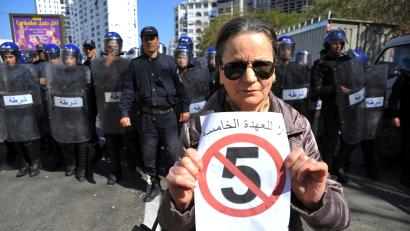 """A woman poses with a sign reading """"No to a 5th turn"""" in front of a line of police officers as she demonstrates with others to denounce President Abdelaziz Bouteflika's bid for a fifth term, Friday, March 1, 2019. Tens of thousands of protesters marched through Algeria's capital Friday against ailing President Abdelaziz Bouteflika's bid for a fifth term, surging past a barricade and defying repeated volleys of tear gas fired by police during the tense demonstration."""