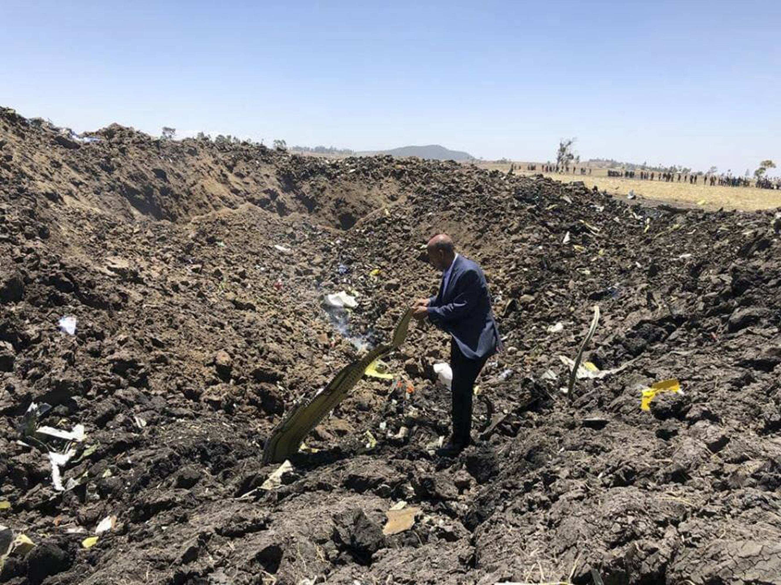 In this photo taken from the Ethiopian Airlines Facebook page, the CEO of Ethiopian Airlines, Tewolde Gebremariam, looks at the wreckage of the plane that crashed shortly after takeoff from Addis Ababa, Ethiopia, Sunday March 10, 2019. An Ethiopian Airlines flight crashed shortly after takeoff from Ethiopia's capital on Sunday morning, killing all 157 people thought to be on board, the airline and state broadcaster said, as anxious families rushed to airports in Addis Ababa and the destination, Nairobi.