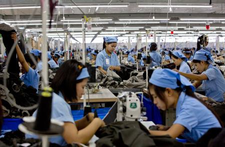 In this Sept. 29, 2015 photo, workers in the Great Forever factory stitch clothes in the Hlaing Tharyar industrial zone outside Yangon, Myanmar. After decades of isolation and underdevelopment, the lack of even basic industries means apparel makers must import everything they use to make garments: thread, cloth, zippers, buttons. (AP Photo/Gemunu Amarasinghe)